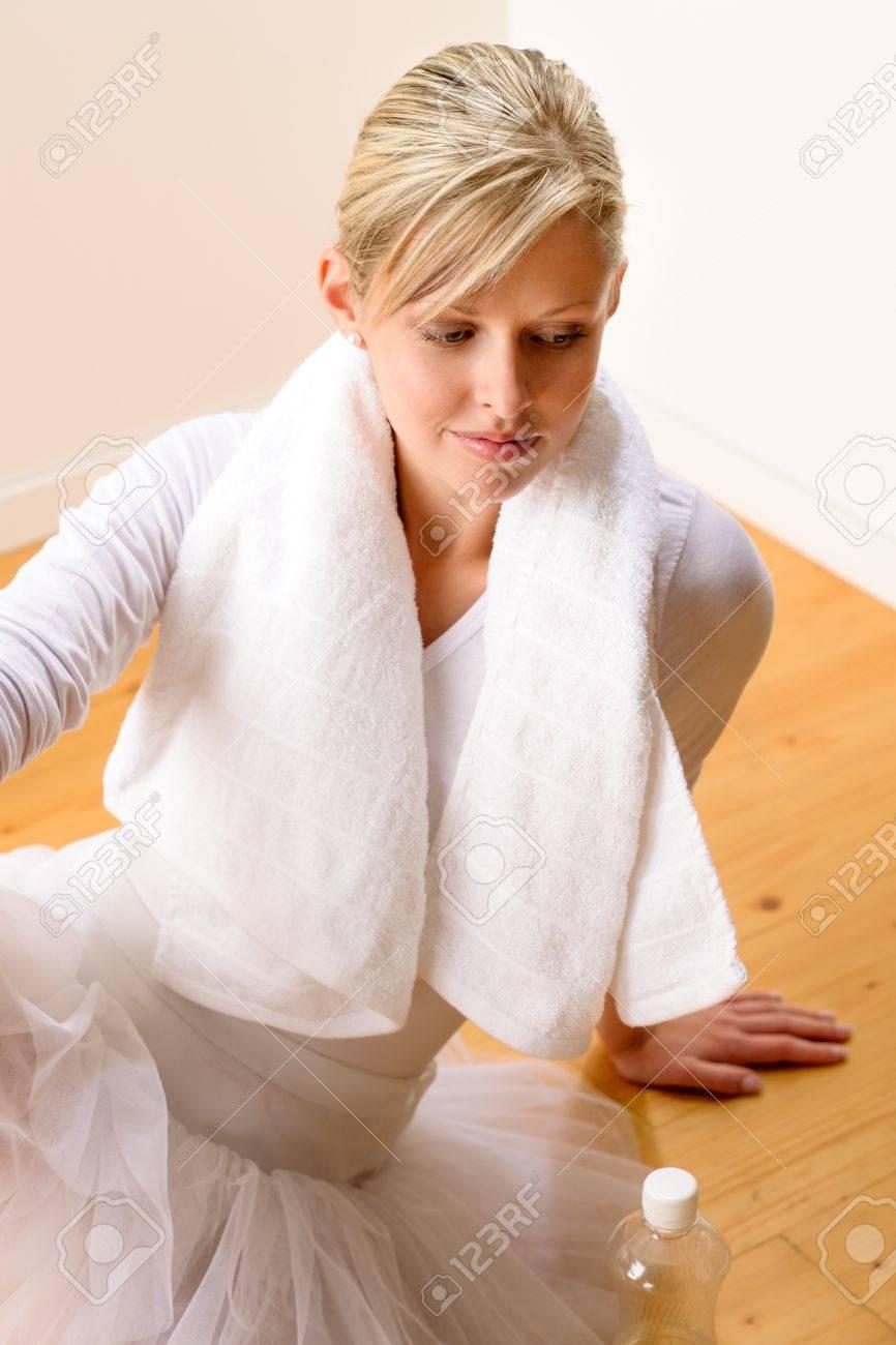 Tired ballerina with towel around her neck resting on floor Stock Photo - 16984863