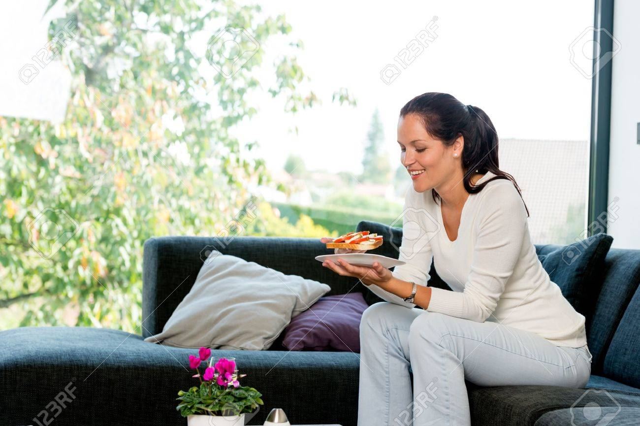 Cheerful woman eating homemade sandwich living room couch sofa Stock Photo - 17388920