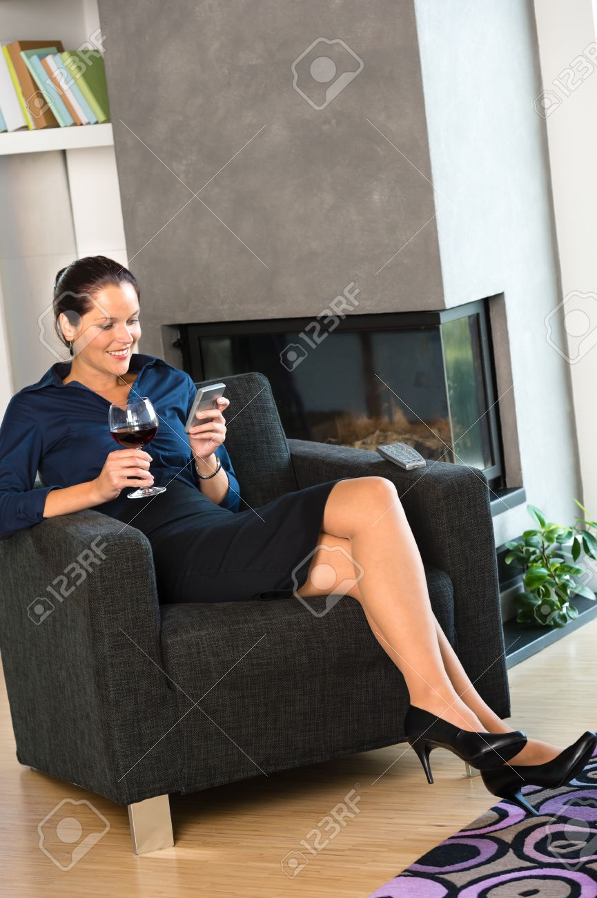 Happy woman relaxing armchair text messaging wine home interior businesswoman Stock Photo - 17388882