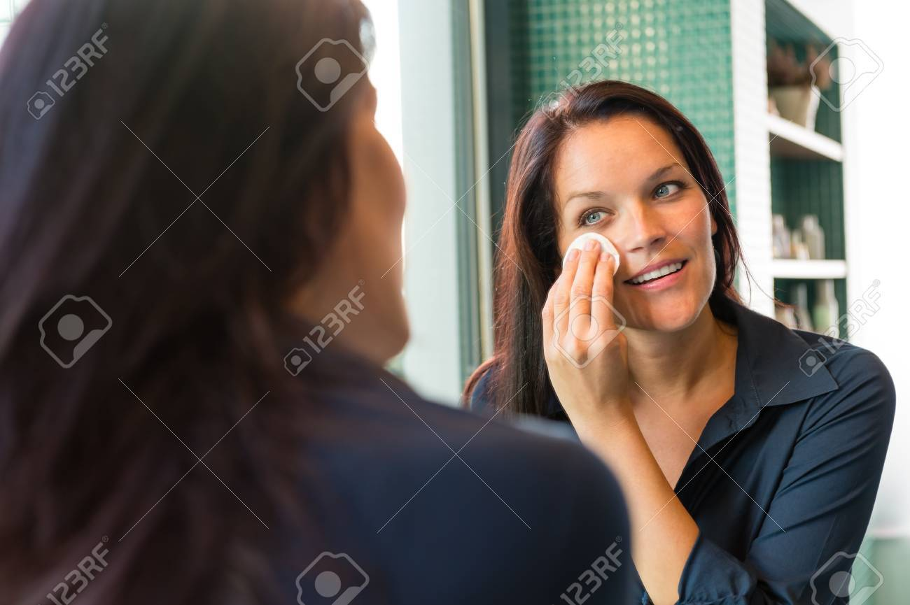 Cheerful woman cleaning face cotton pads bathroom removing cleaning lotion Stock Photo - 17388941