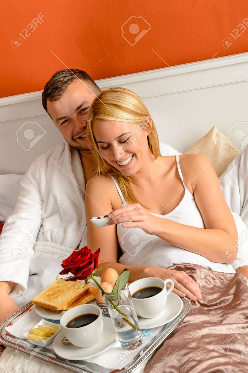 Happy lovers lying bed eating romantic breakfast together morning Stock Photo - 17887247