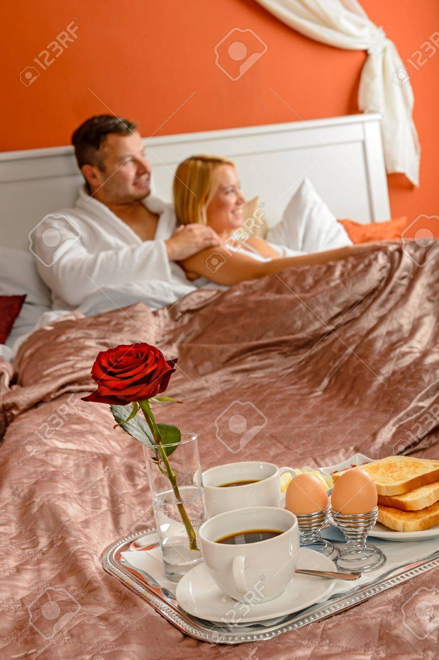 Romantic breakfast hotel room service young couple watching bed Stock Photo - 17887261