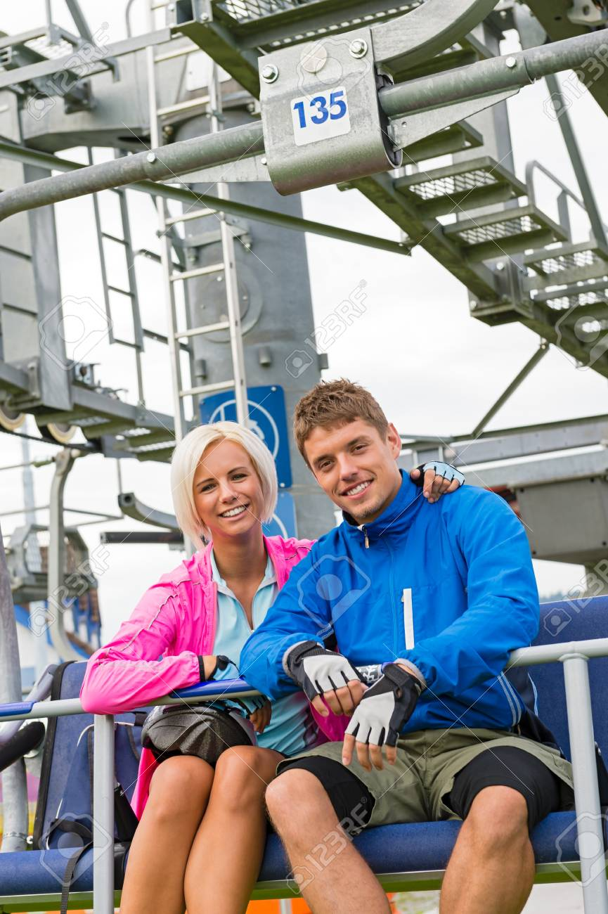 Smiling couple in sweatsuit sitting on char lift in springtime Stock Photo - 18599229
