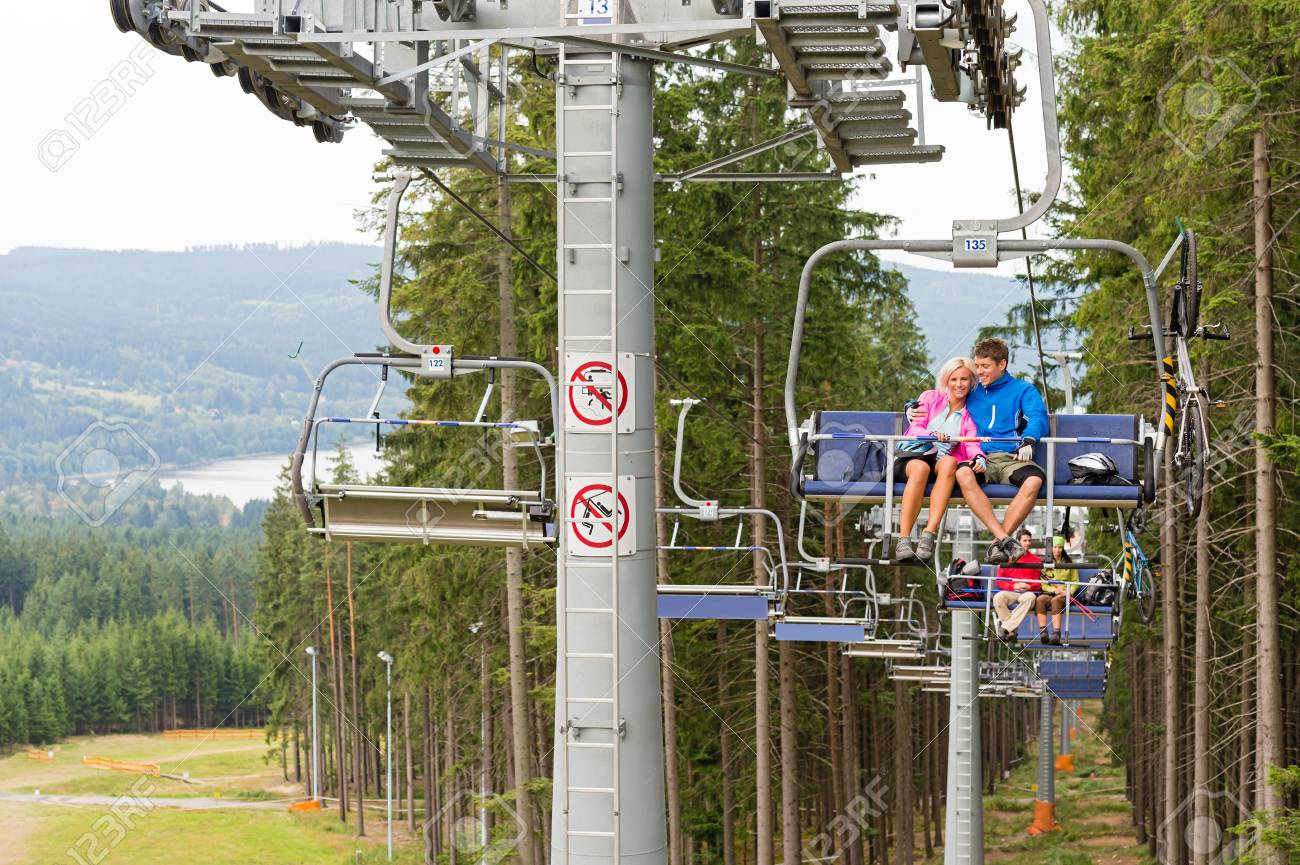 Cuddling couple going through pinewood by chair lift Stock Photo - 18600838