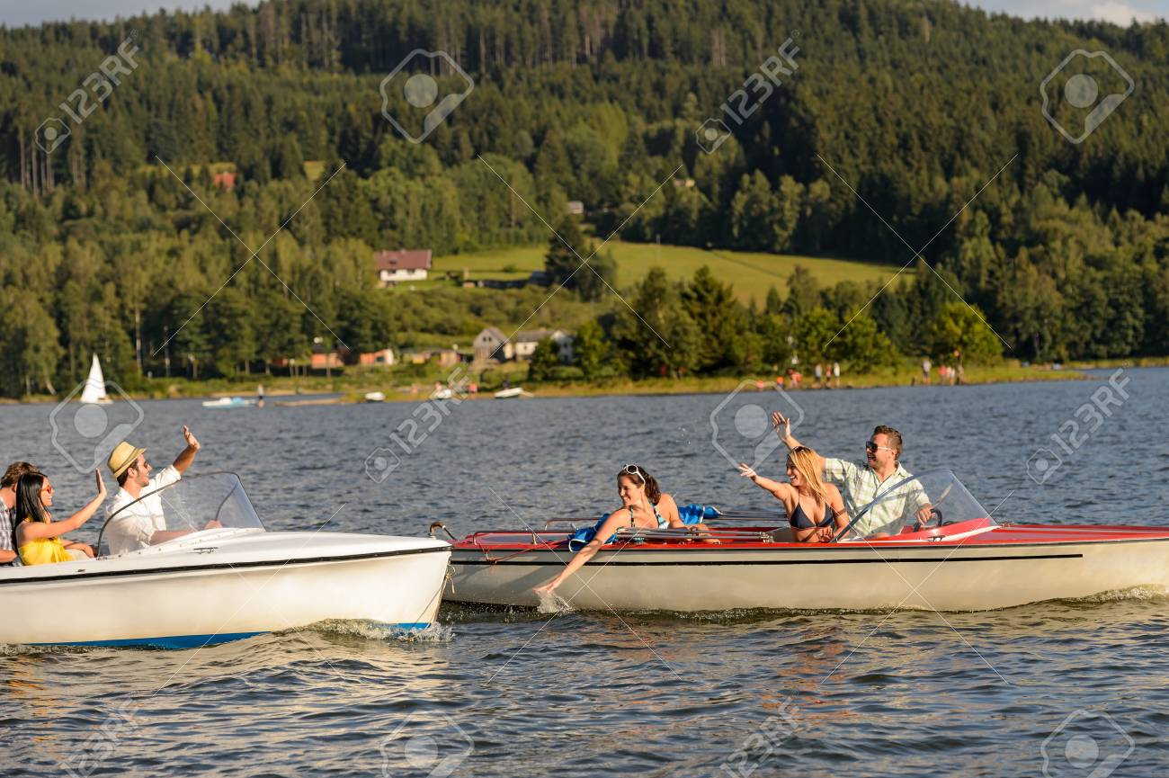 Young friends having fun in motorboats waving and splashing water Stock Photo - 18881767