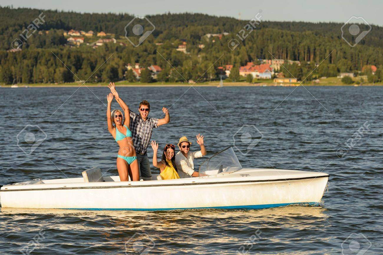 Young friends waving from speed boat in the sunshine Stock Photo - 18867098