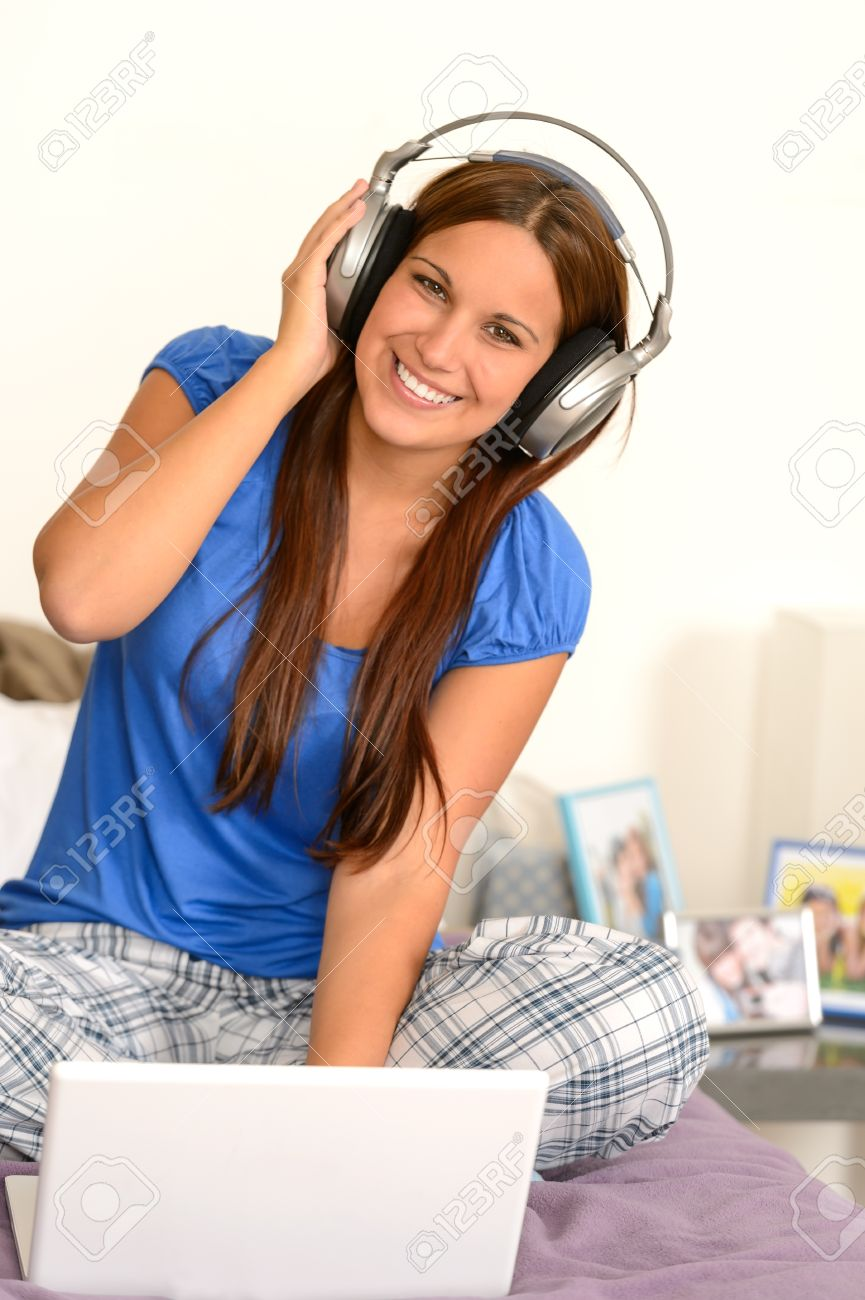 Cheerful teenager girl listening music with headphones on laptop Stock Photo - 18853450