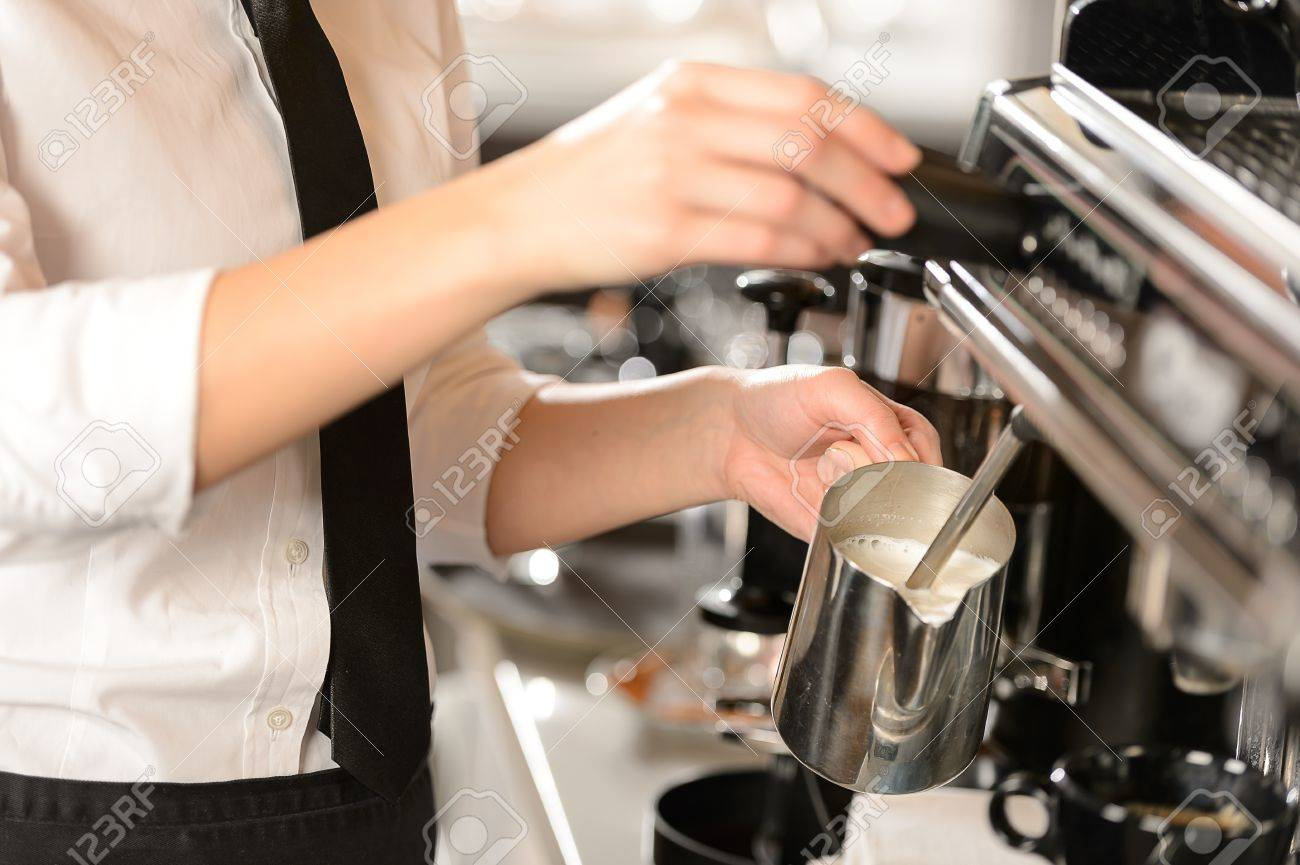 Barista steaming milk for hot cappuccino with machine Stock Photo - 19379810