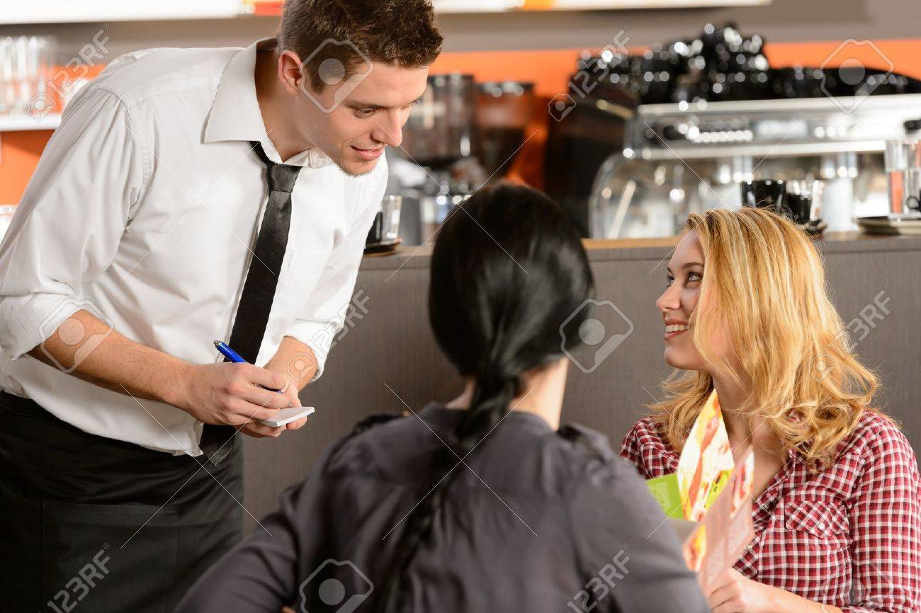 Waiter taking orders from young woman customer in restaurant Stock Photo - 19379820