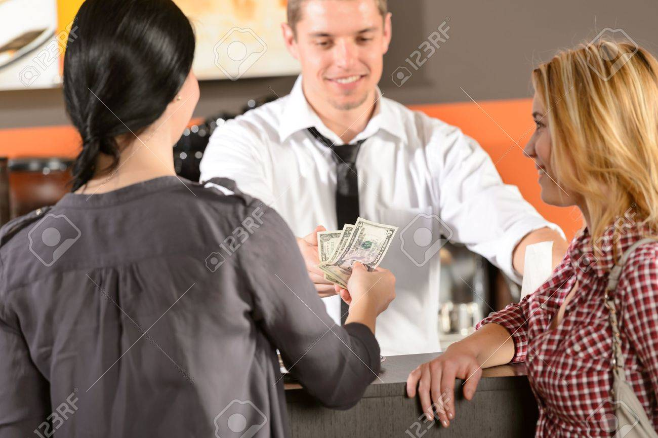 Female customers paying by cash dollar in bar to bartender Stock Photo - 19379803