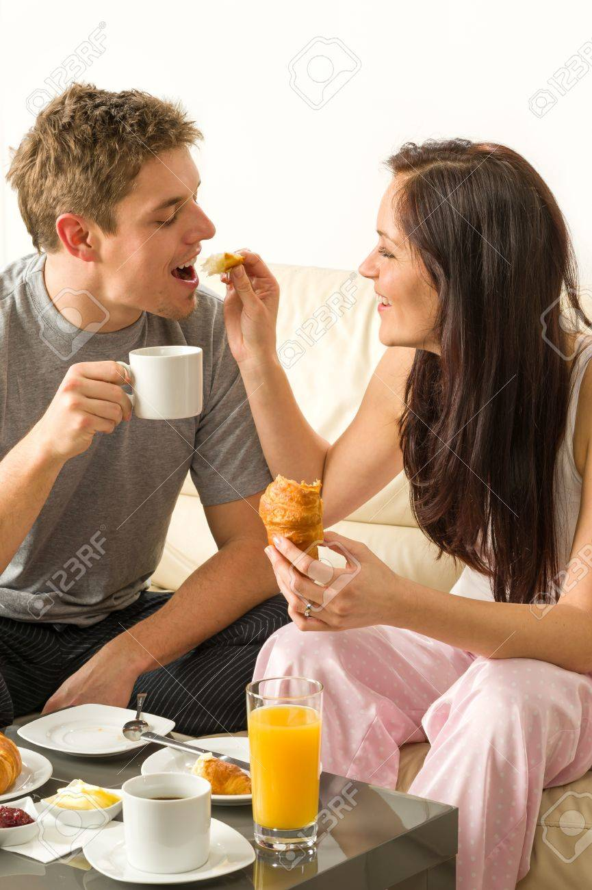 Carefree couple eating breakfast in pajamas at home Stock Photo - 20142144