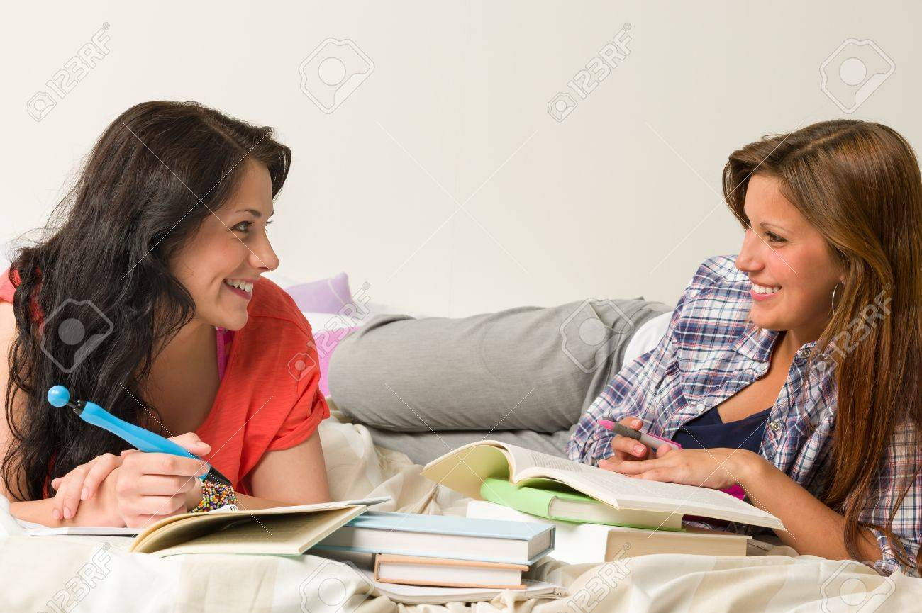 Happy classmates lying on bed and learning at dorm Stock Photo - 20244525