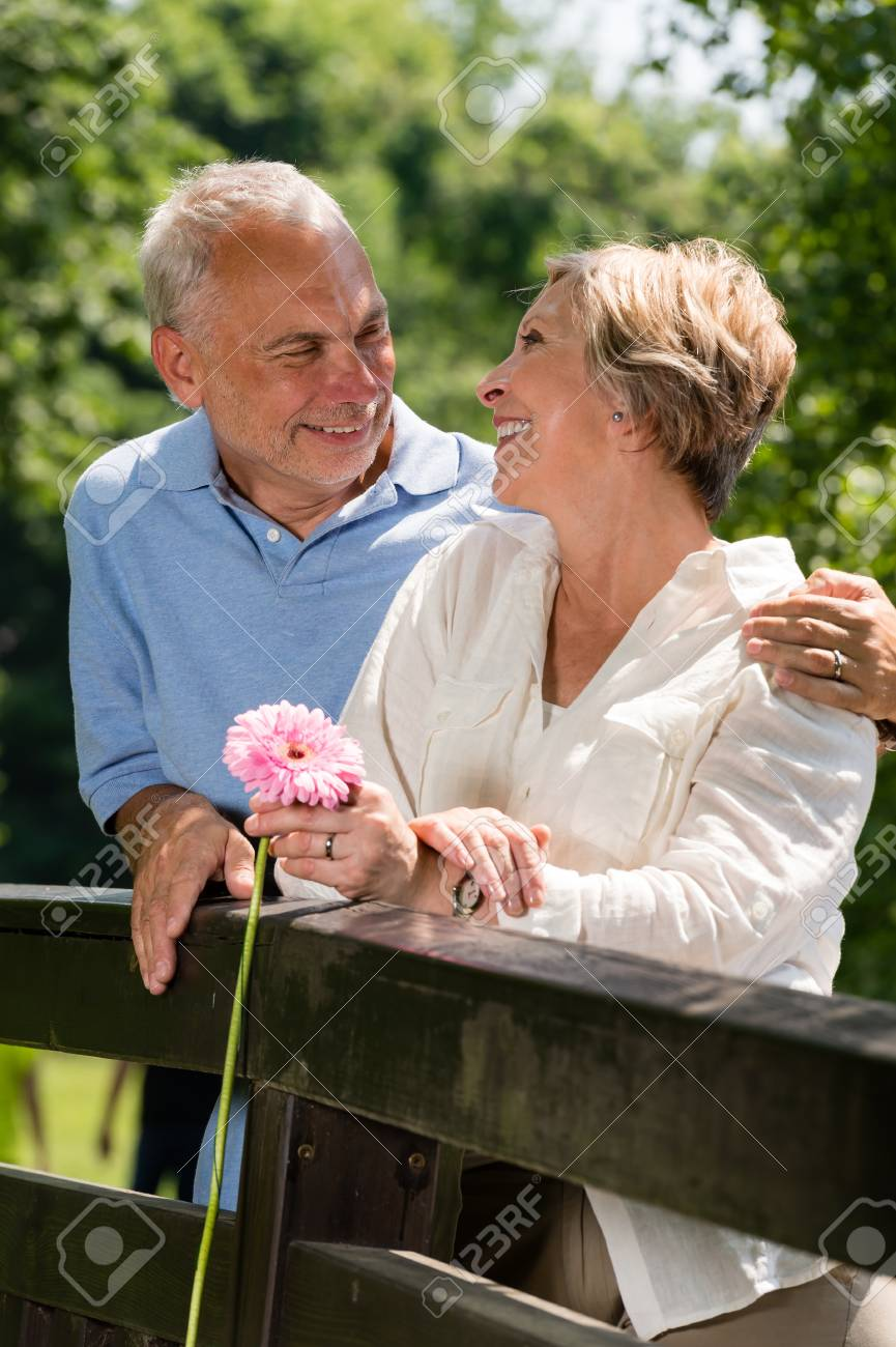 Romantic senior couple laughing at each other outdoors Stock Photo - 21302818