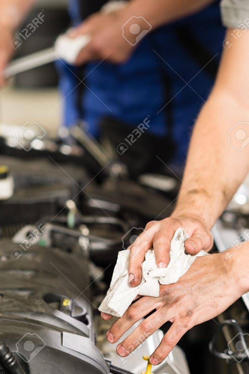 Car mechanic wiping his dirty hands with cloth Stock Photo - 21738131