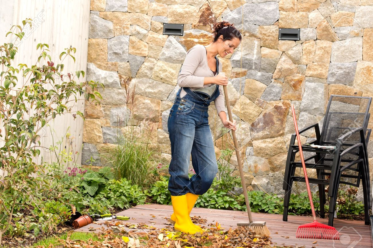 Backyard Cleaning young woman sweeping autumn leaves veranda backyard cleaning.. stock