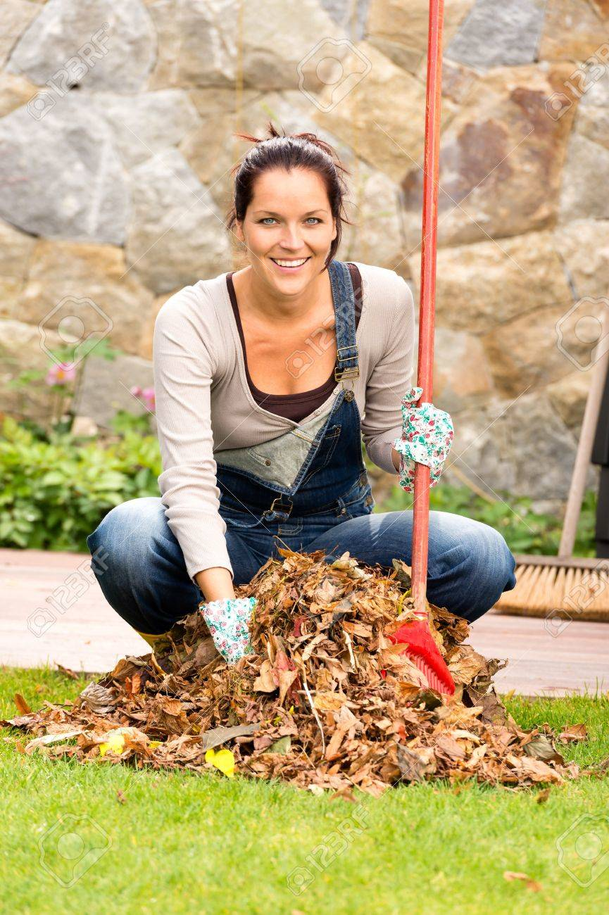 Cheerful woman sweeping leaves fall pile backyard housework outdoor Stock Photo - 22144325