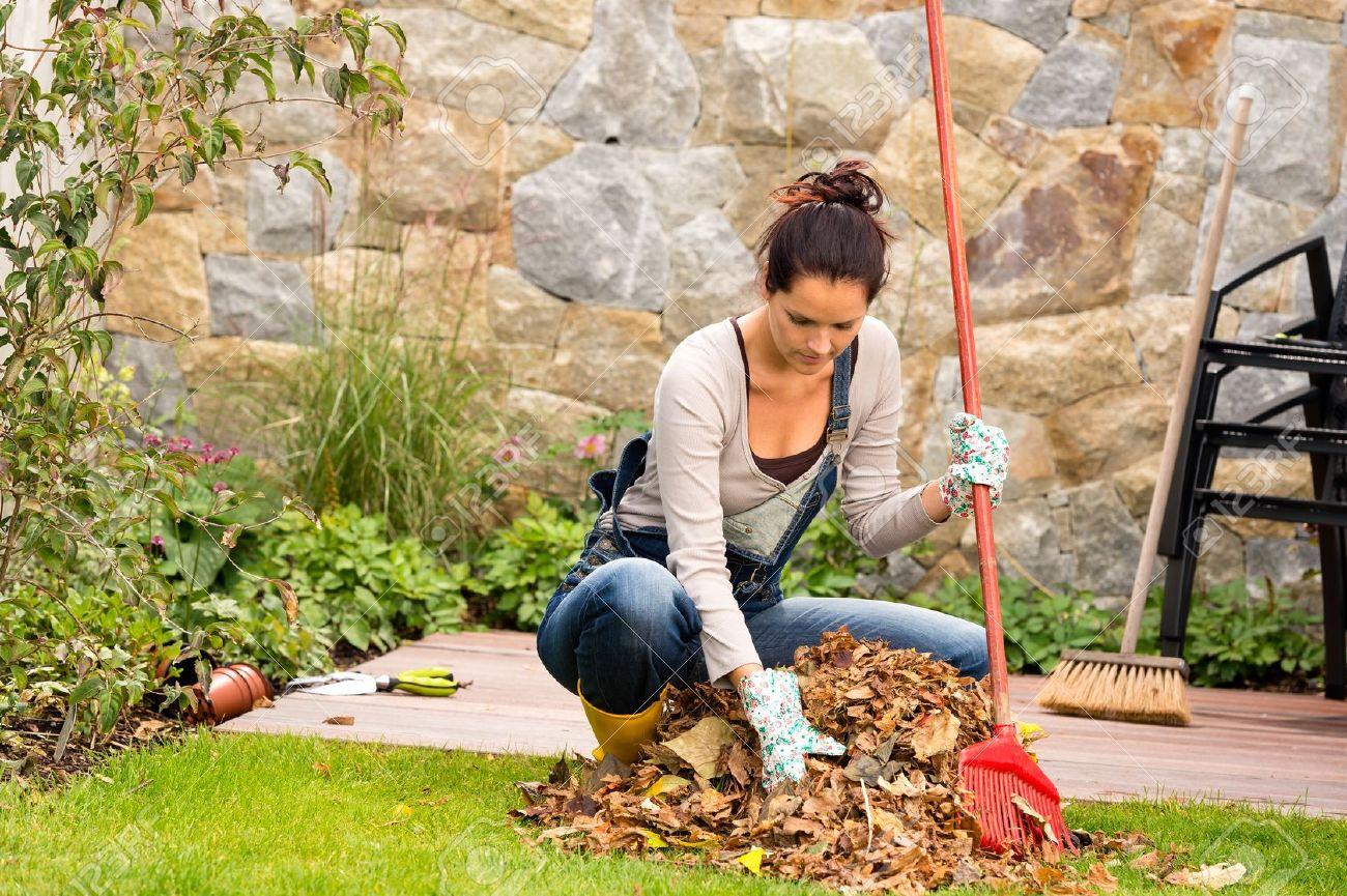 Young woman raking leaves autumn pile garden veranda housework sweeping Stock Photo - 22144327