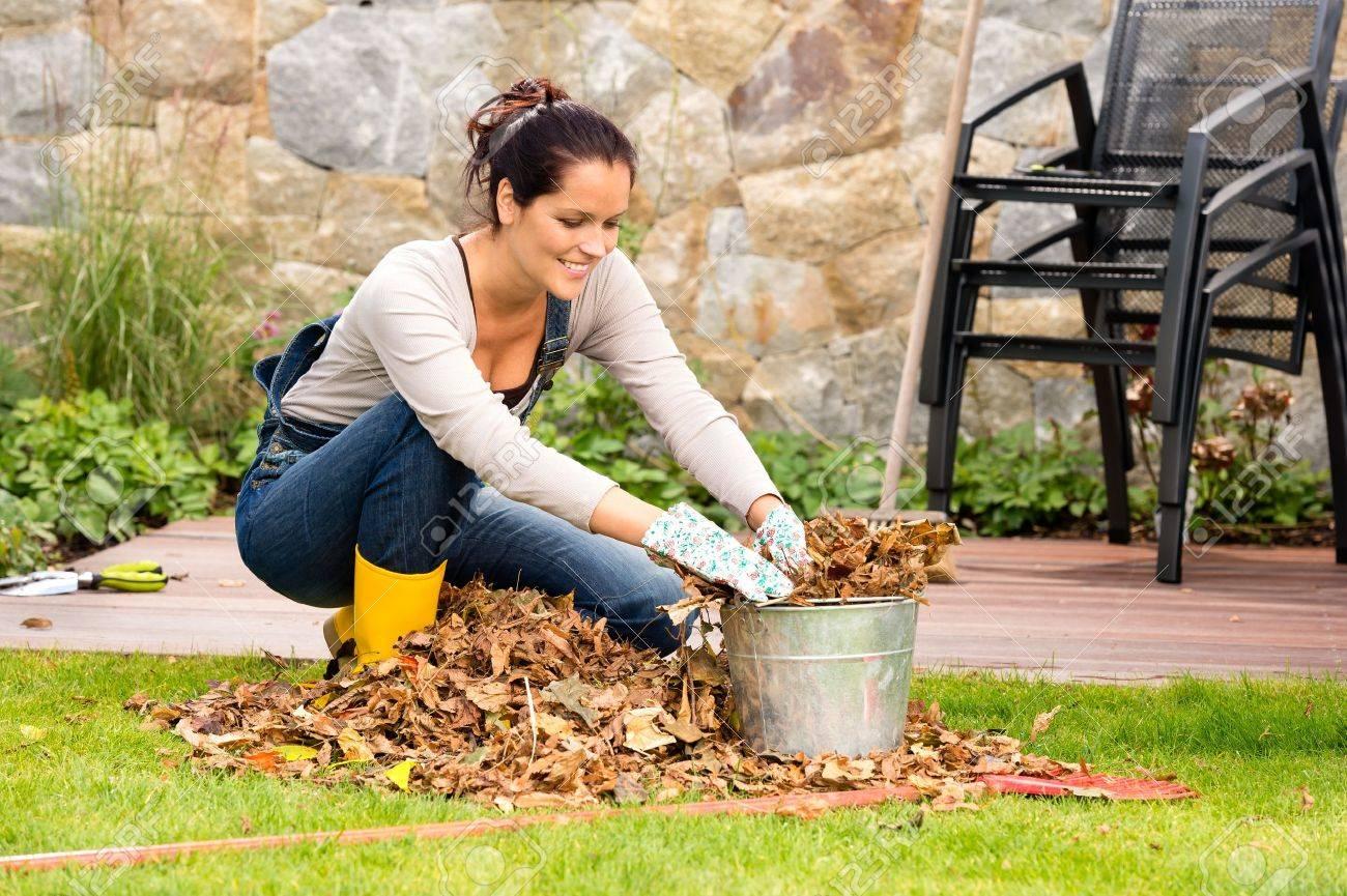 Femme souriante farce feuilles sèches dans le seau automne ménage de jardin Banque d'images - 22144328