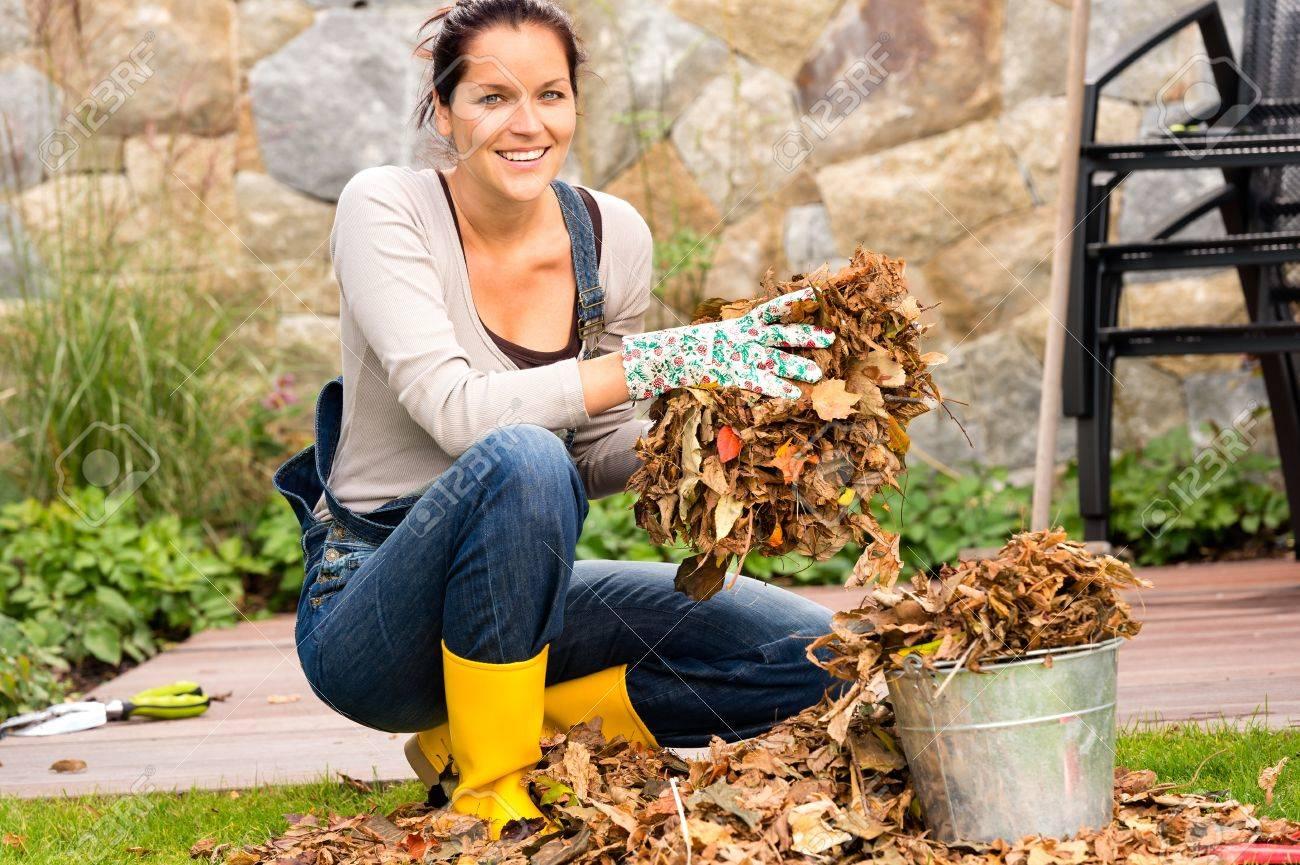 Femme souriante posant les feuilles dans un seau chute ménage de jardin Banque d'images - 22144329