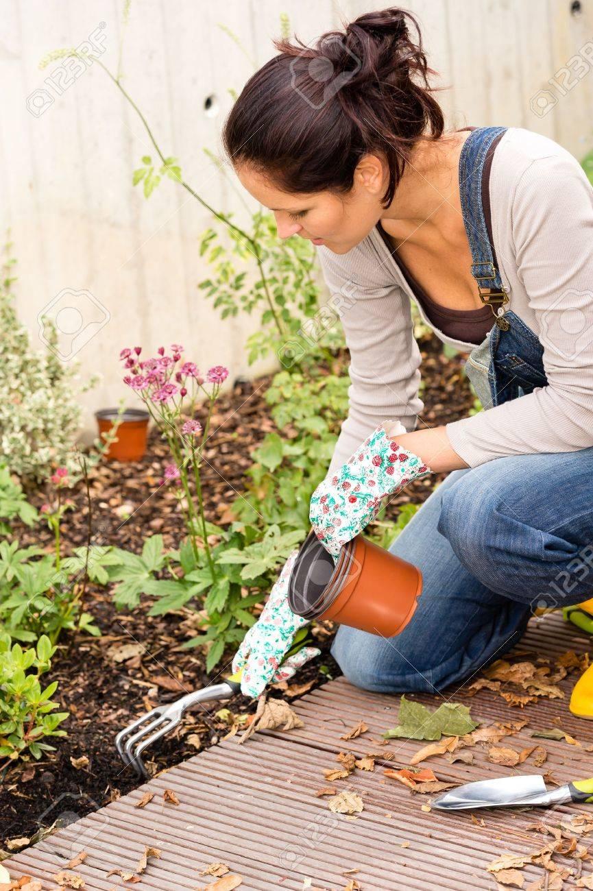 Femme agenouillée plantation automne jardin cour passe râteau plantes travaux ménagers Banque d'images - 22144335