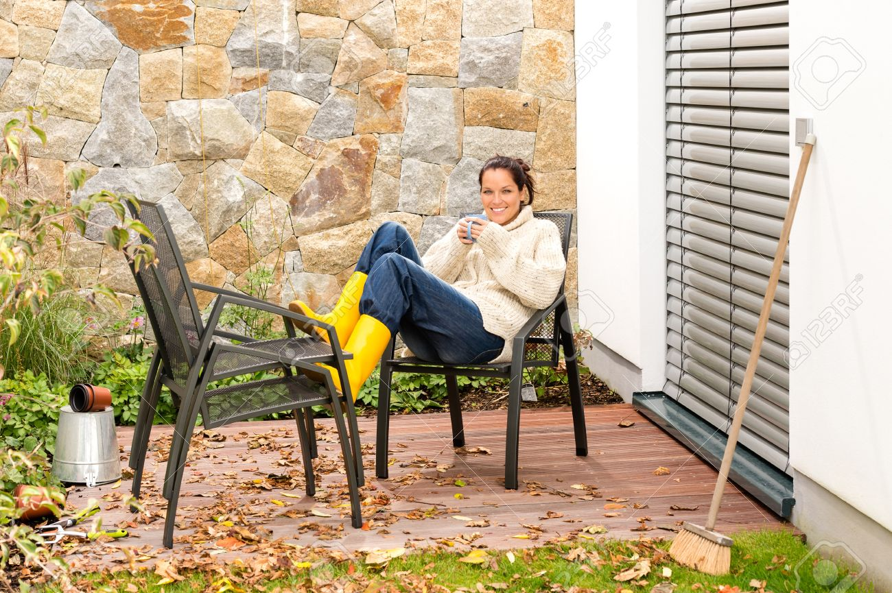 Happy woman relaxing autumn housework drinking coffee fall patio Standard-Bild - 22144338