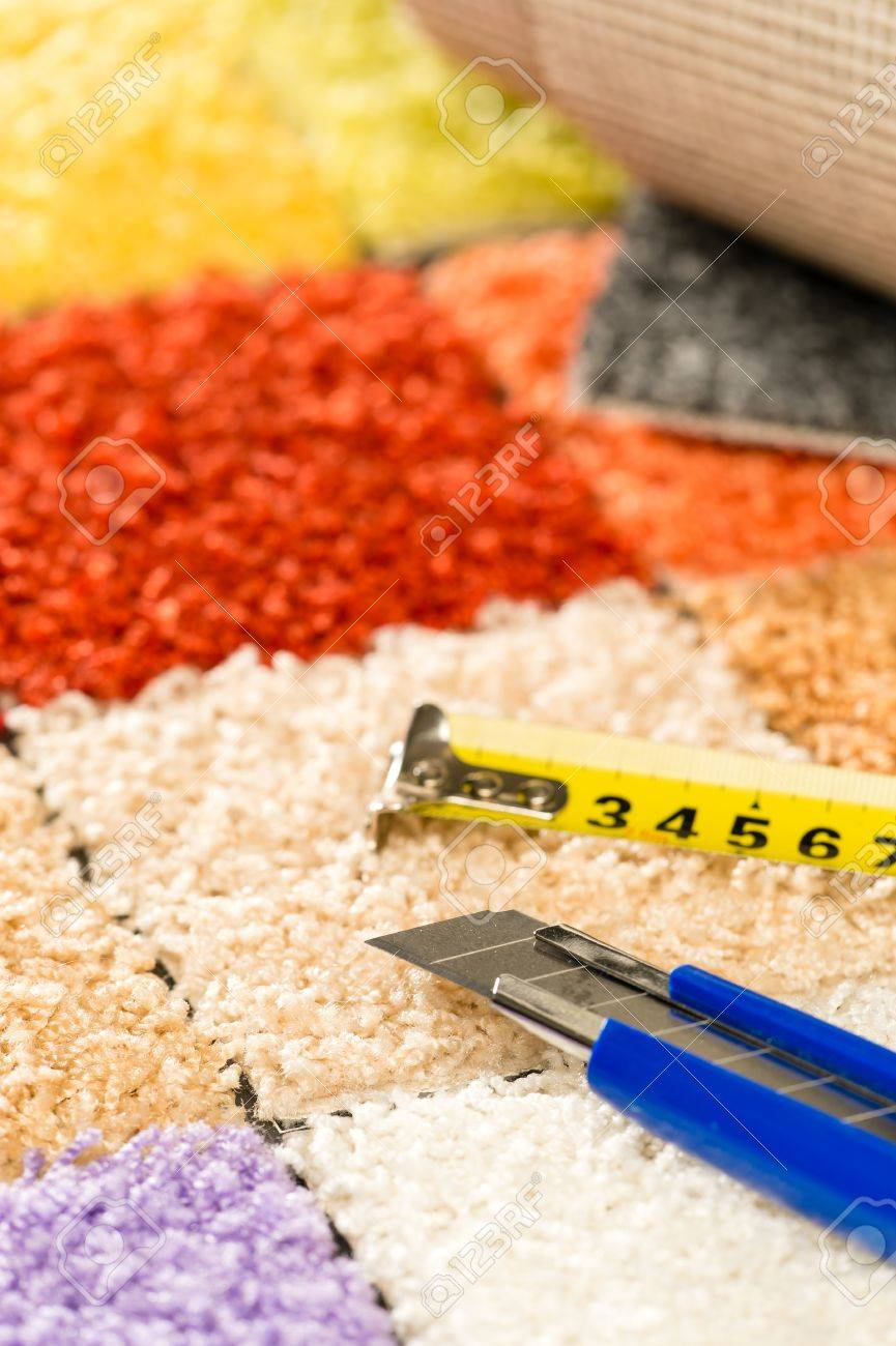 Colorful carpet swatches, tape measure and  boxcutter Stock Photo - 22144402