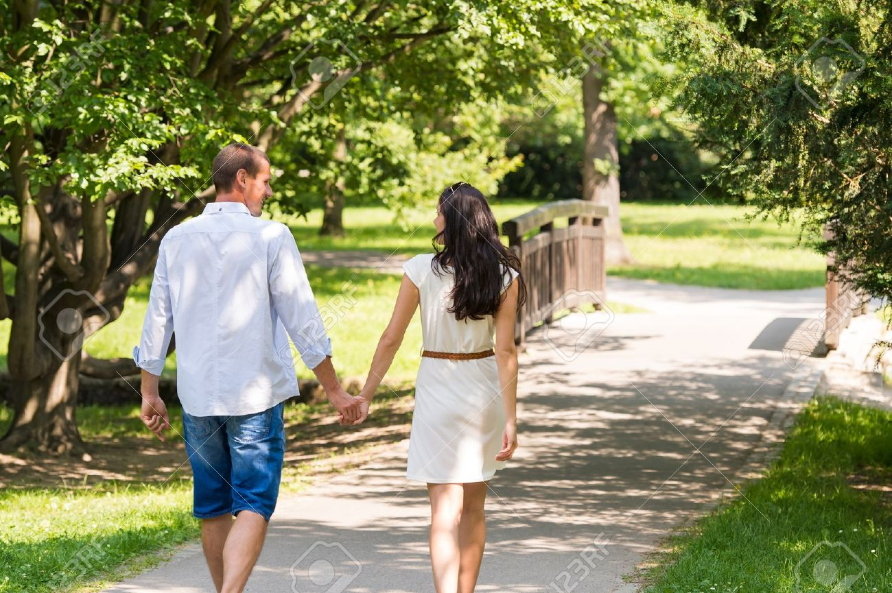 Rear view of walking caucasian couple in park Standard-Bild - 22213547