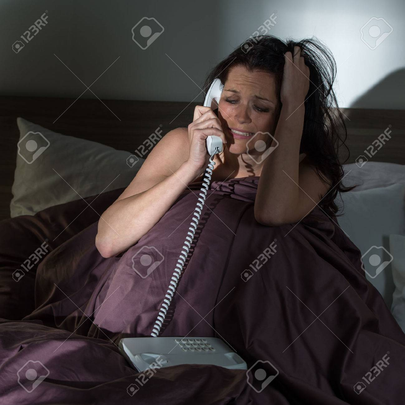 Crying young woman calling phone in bed Stock Photo - 23701311