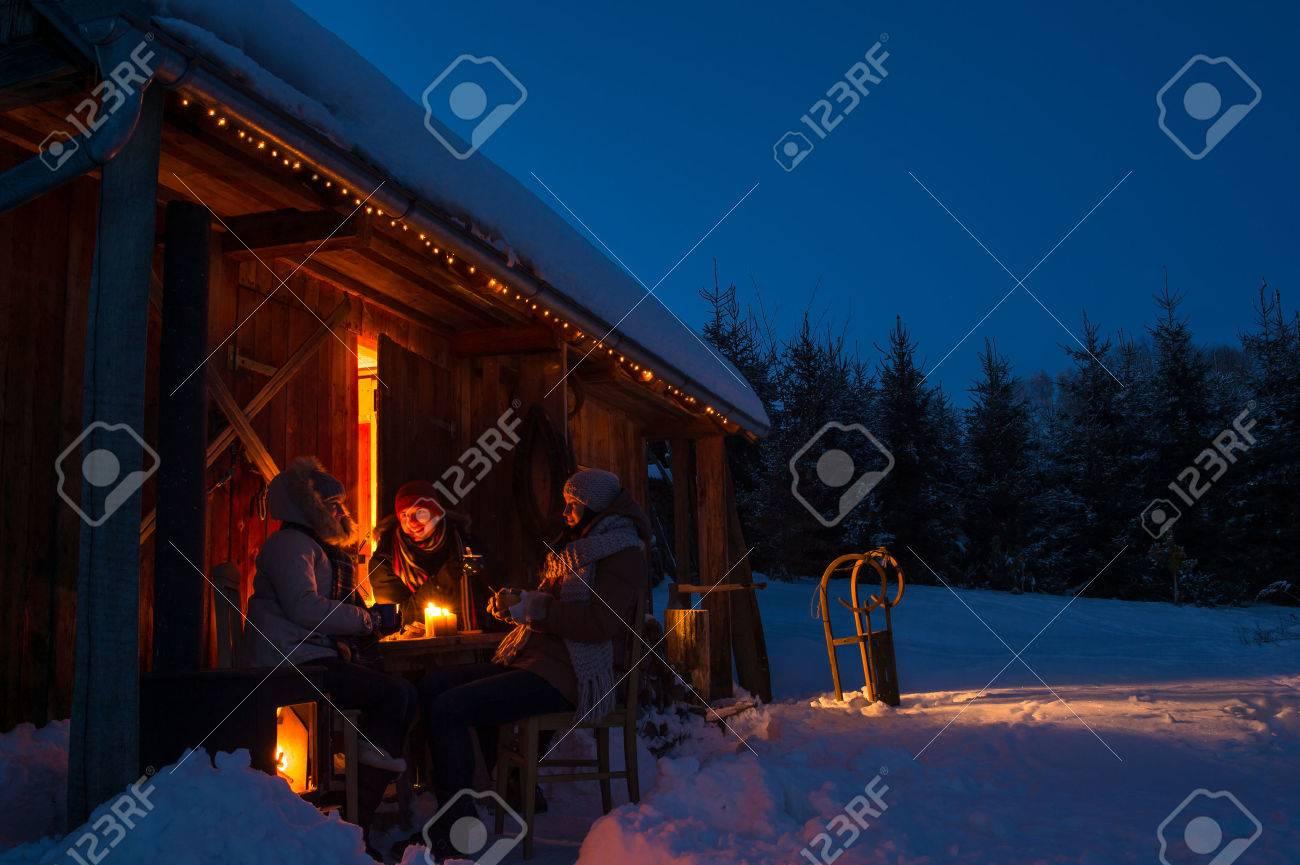 Evening winter cottage friends enjoy hot drinks in snow countryside Standard-Bild - 23539218