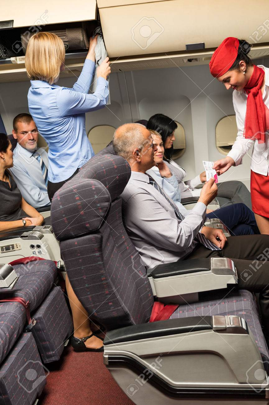 Flight attendant check passenger tickets in plane cabin Standard-Bild - 23714479