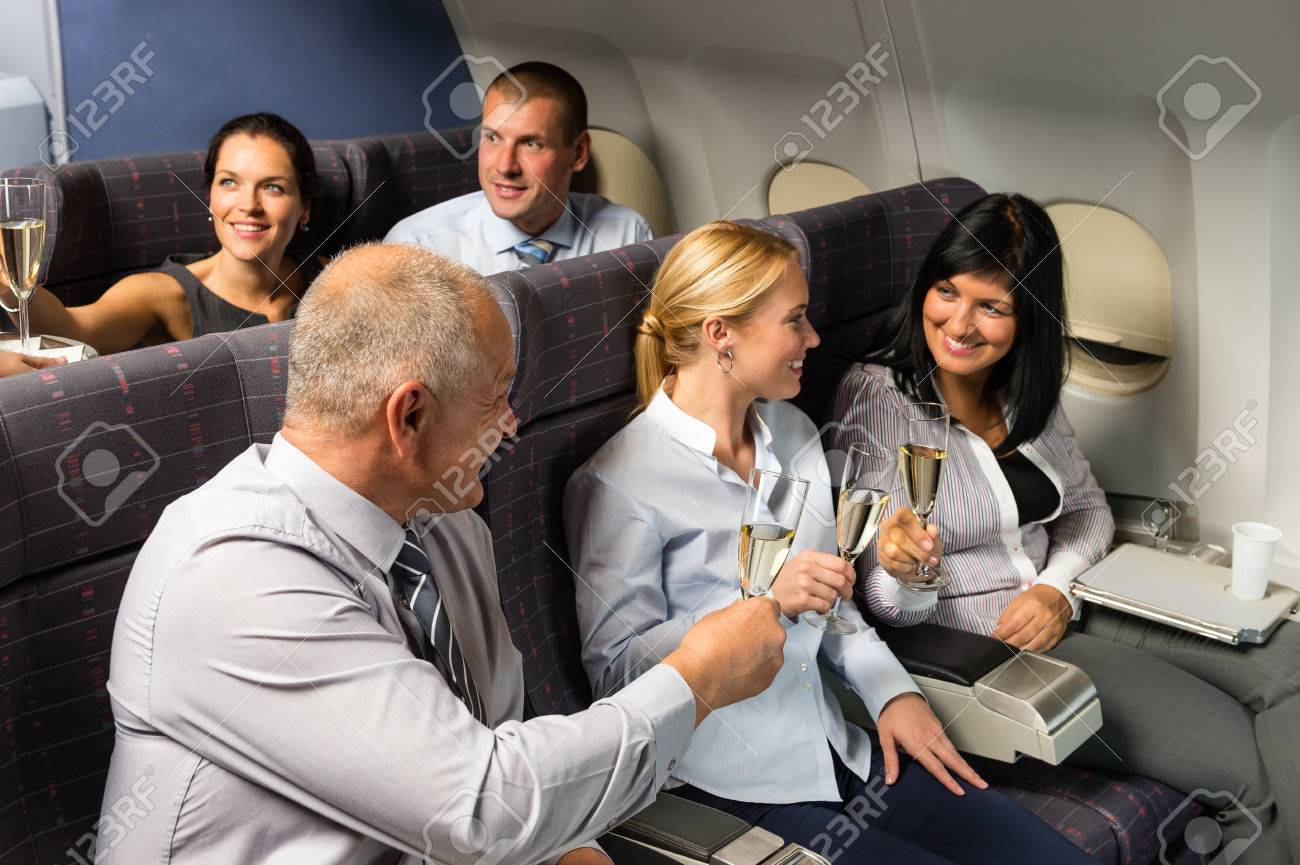 Airplane cabin businesspeople toasting with champagne flight travel passenger Standard-Bild - 23714484