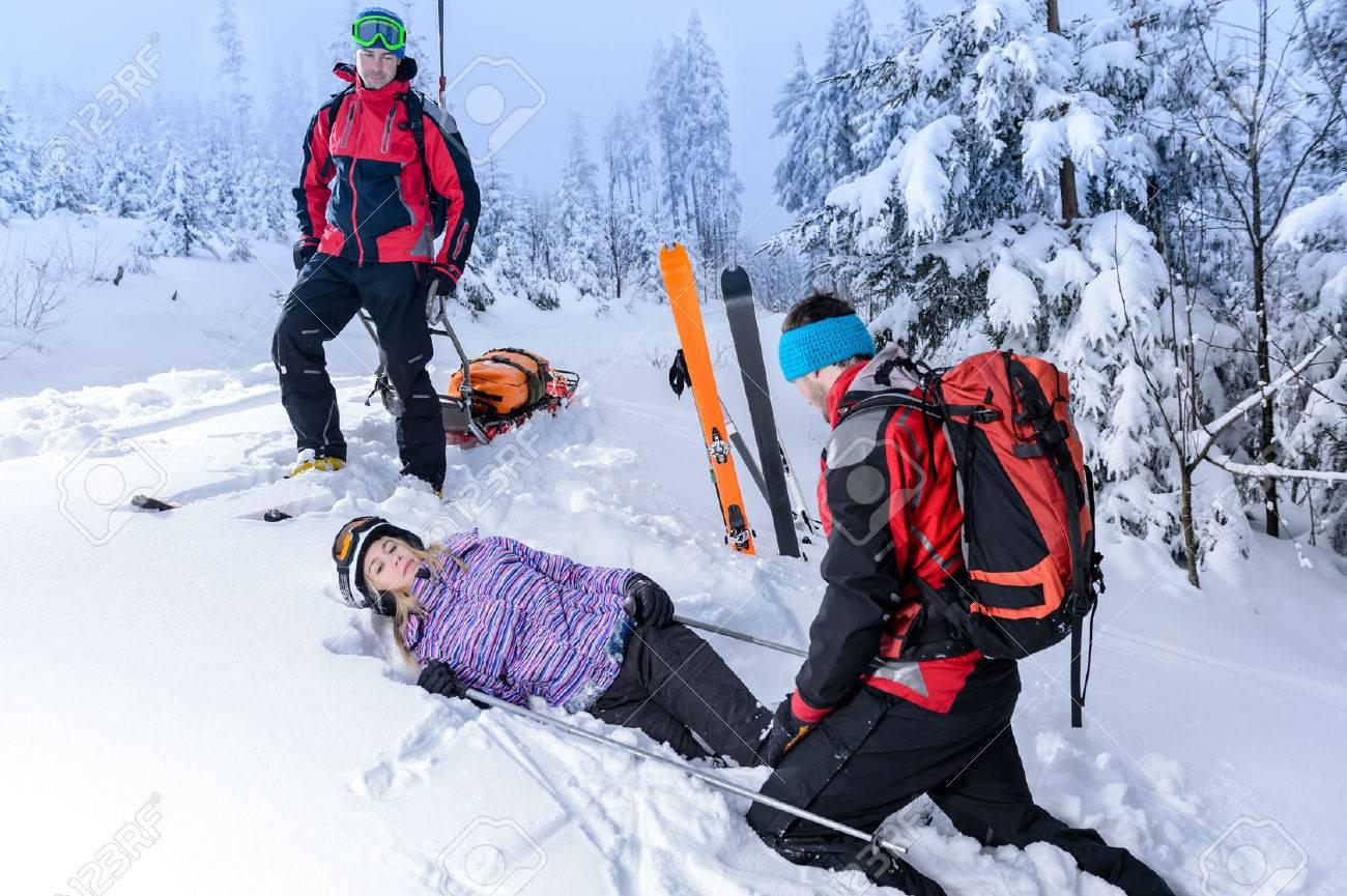 Rescue ski patrol help injured woman skier lying in snow Standard-Bild - 25109380