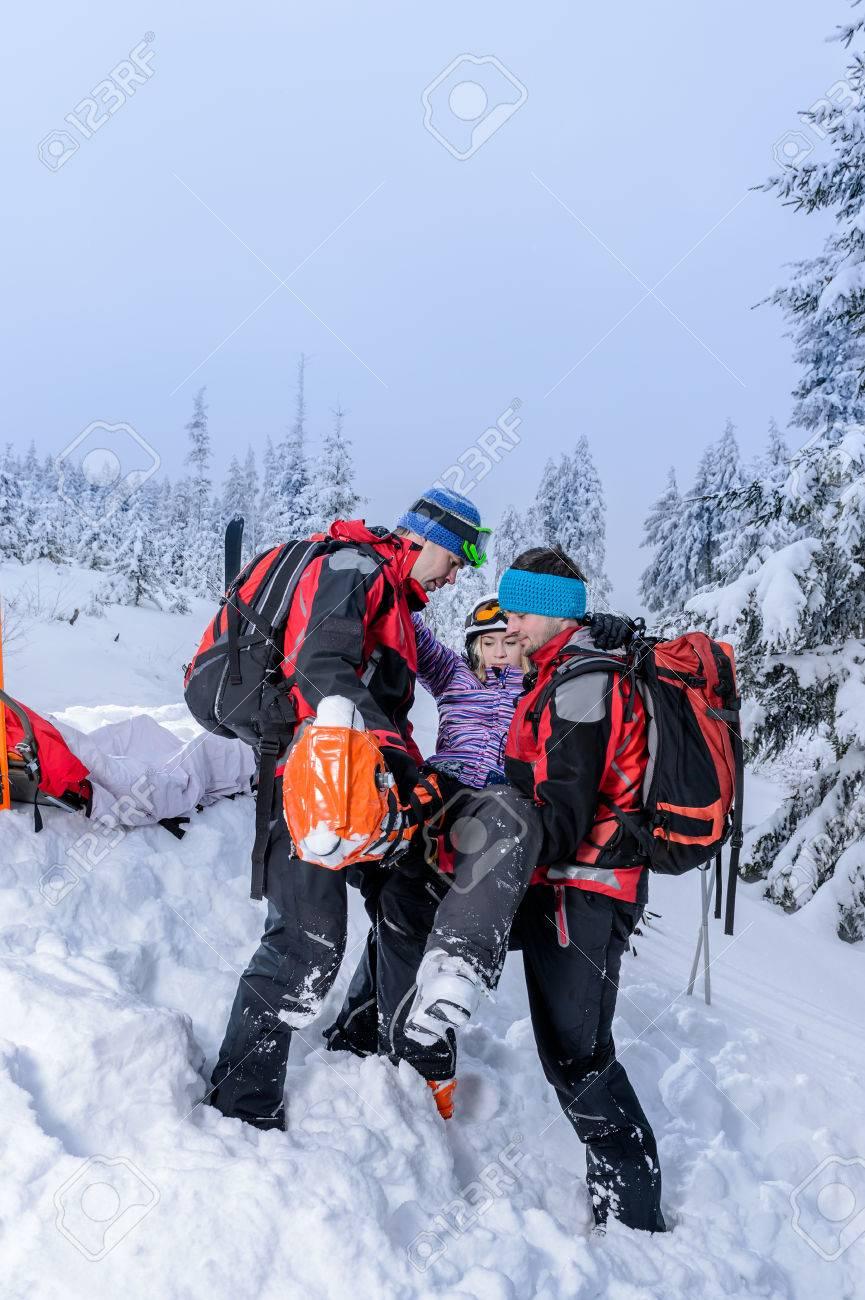 Ski patrol carry injured woman skier on rescue stretcher Standard-Bild - 25109383