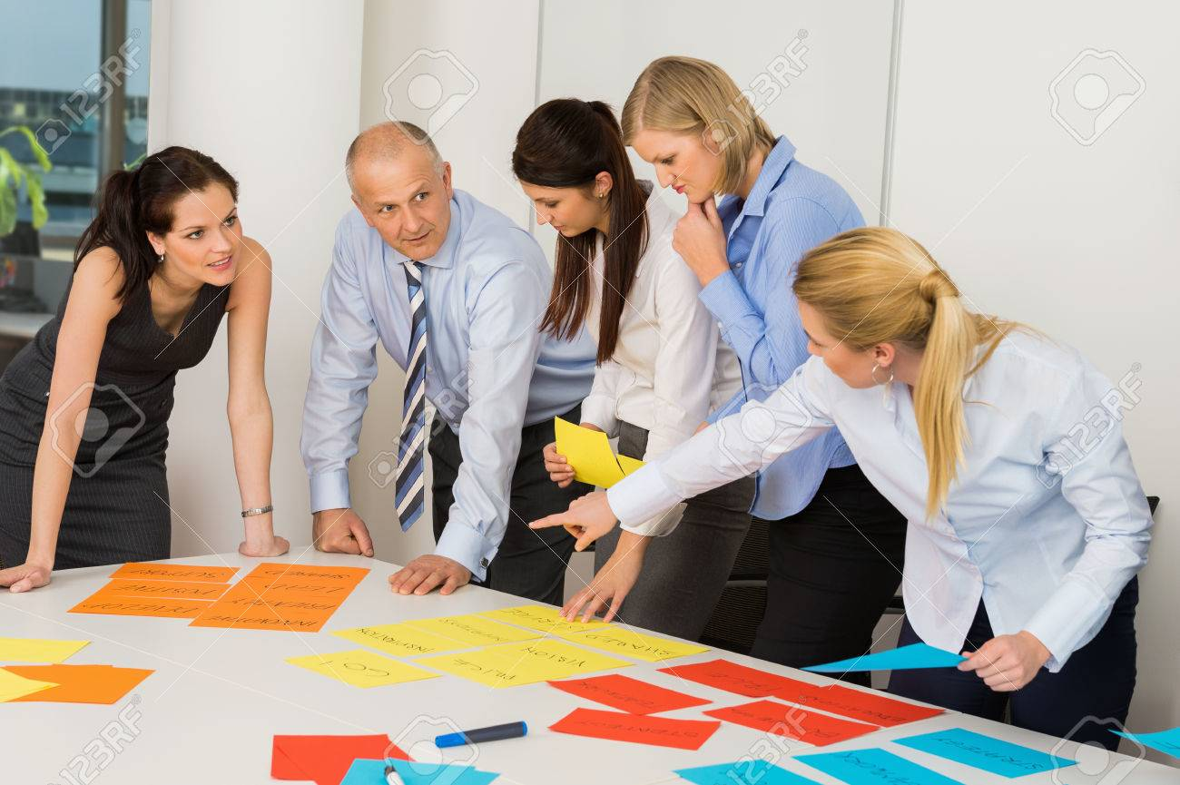 Business team discussing multicolored labels in boardroom meeting Standard-Bild - 27281175