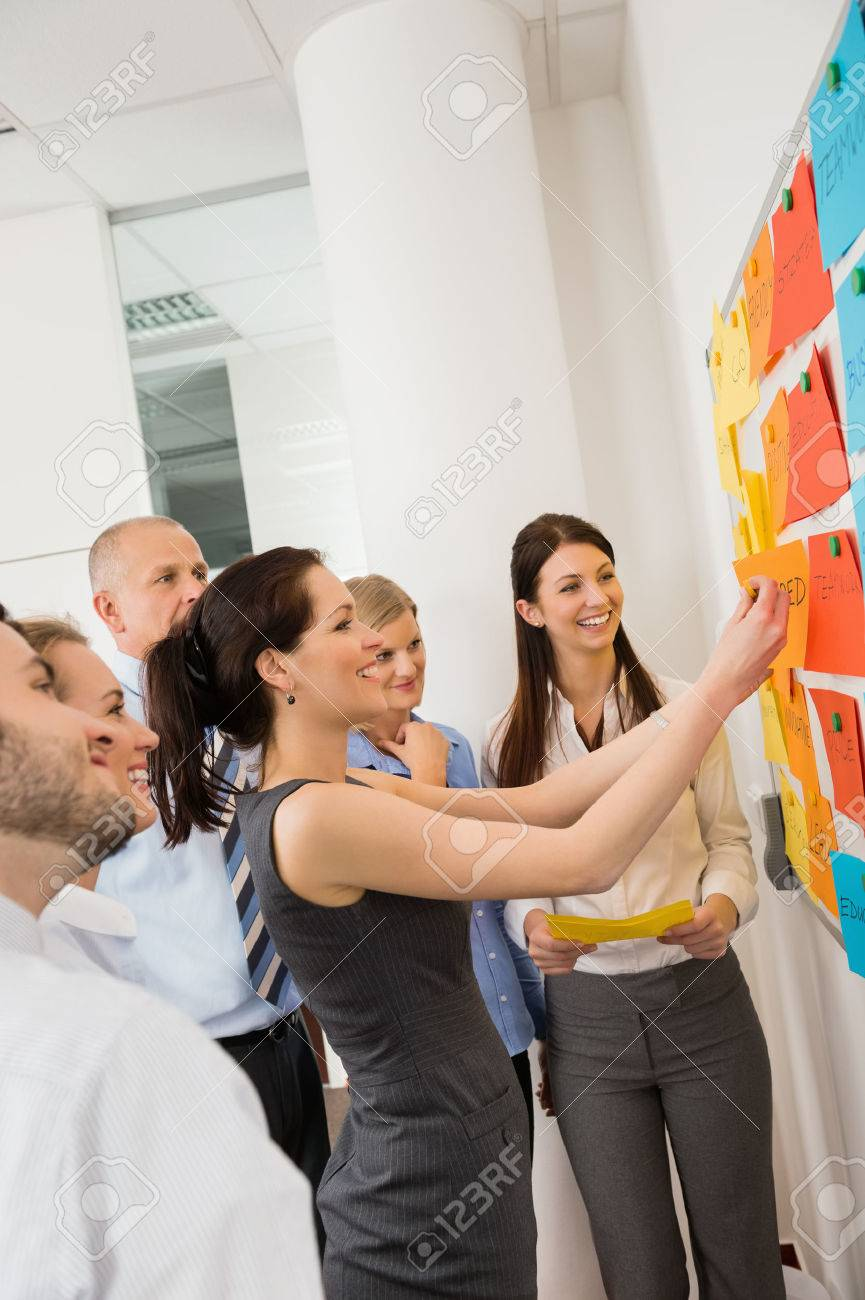 Businesswoman sticking labels on whiteboard during meeting Standard-Bild - 27281140