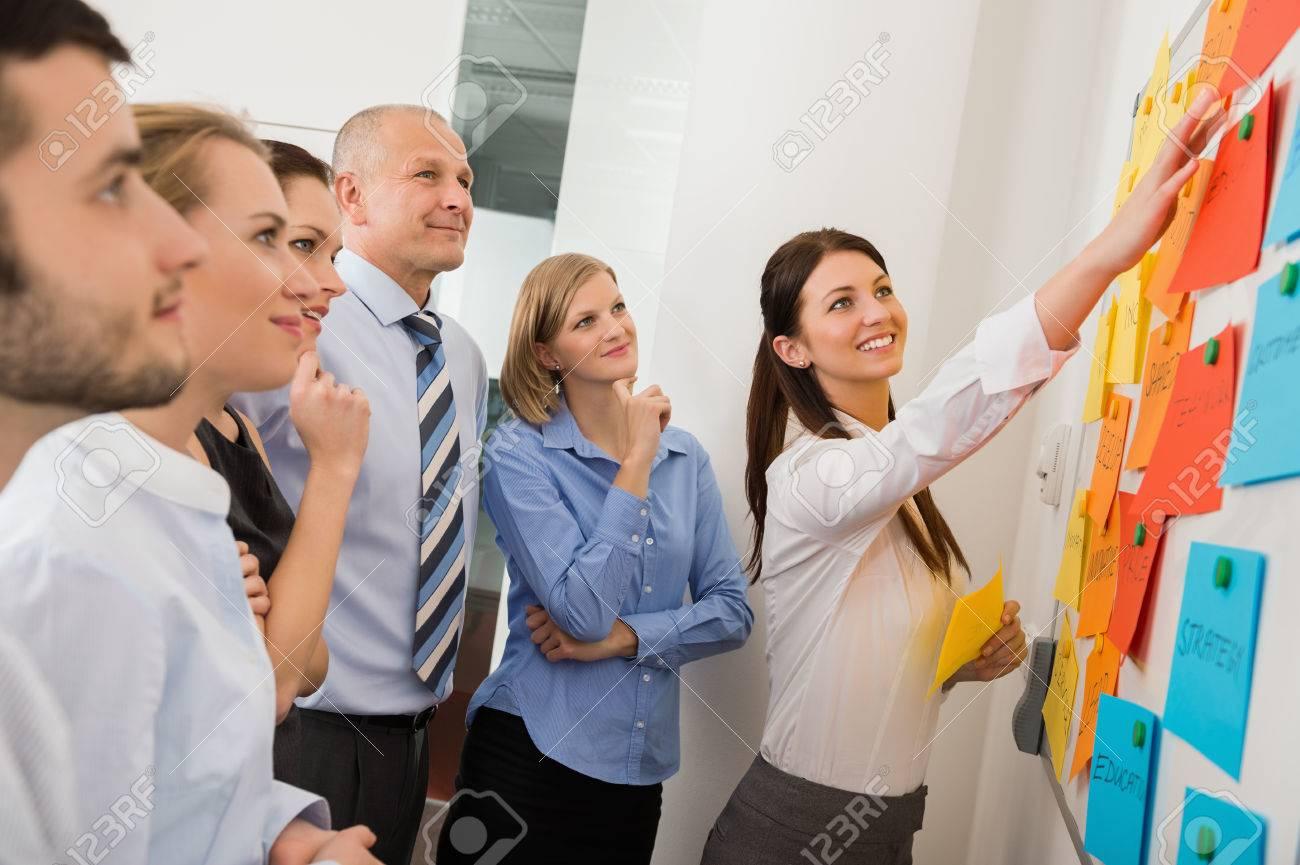 Geschaftsfrau Die Auf Whiteboard In Der Begegnung Mit Buro Kollegen