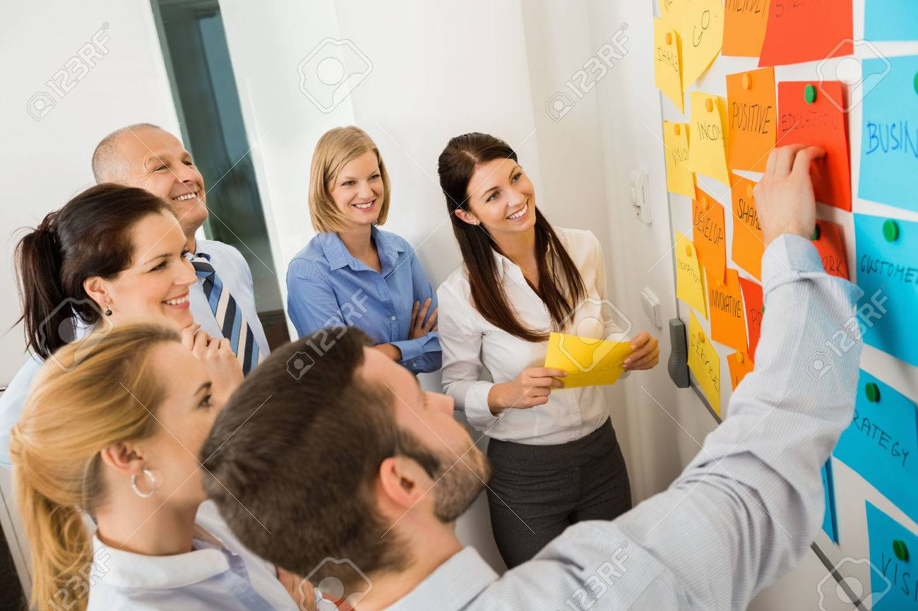 Businessman explaining labels on whiteboard to colleagues in meeting Standard-Bild - 27281142