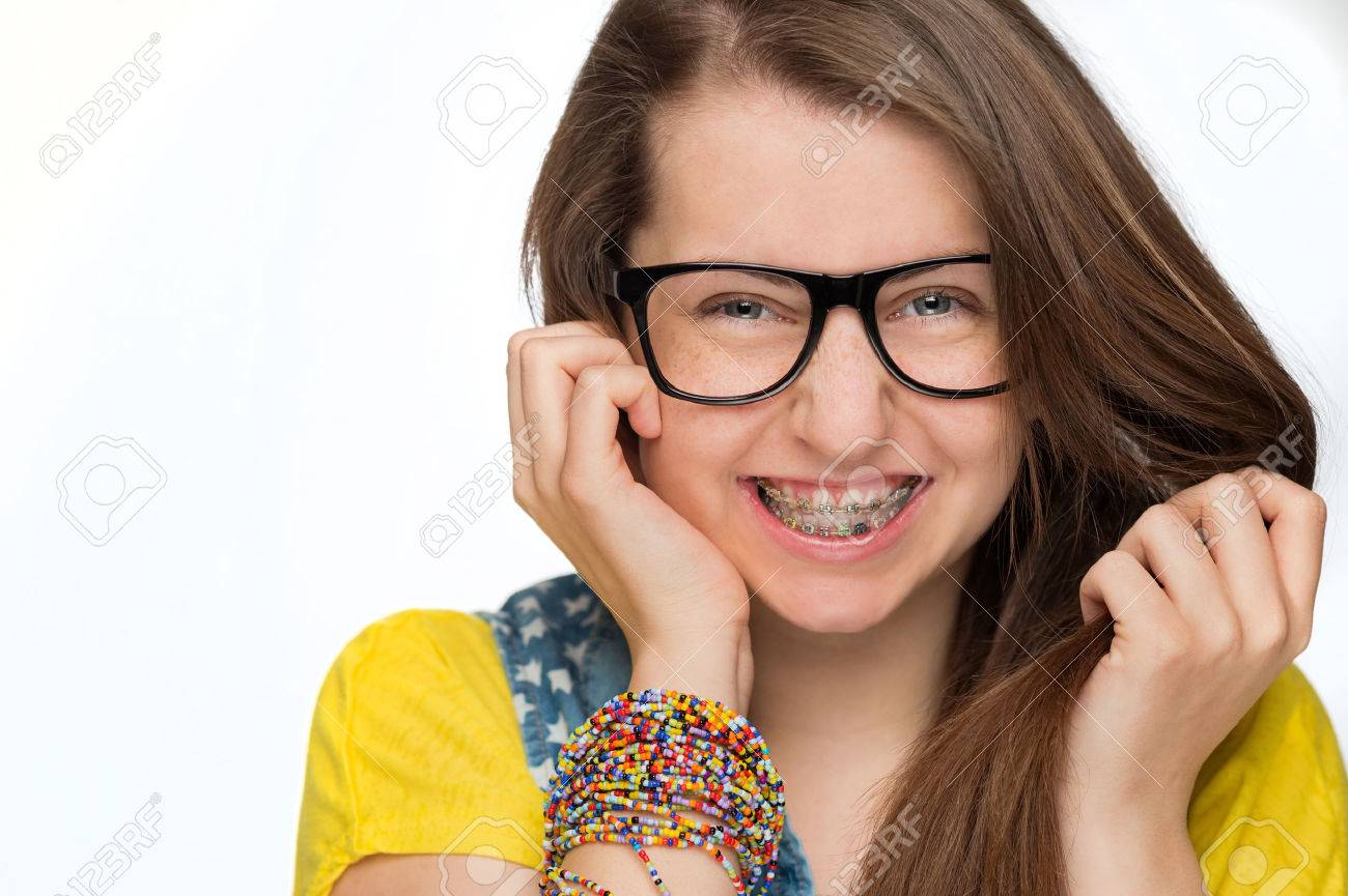 Cheerful girl with braces wearing geek glasses on white background Stock Photo - 27771703