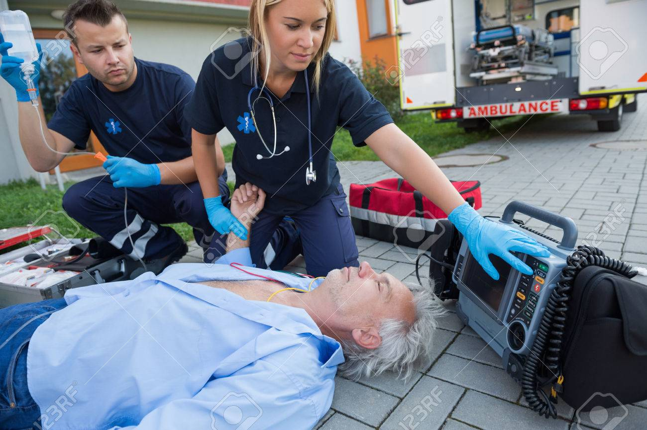 Paramedics checking pulse of unconscious senior man lying on street Stock Photo - 28226030