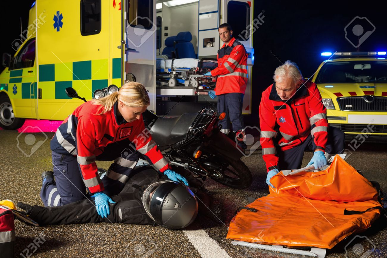 Emergency team assisting injured motorbike man driver at night Stock Photo - 28226080