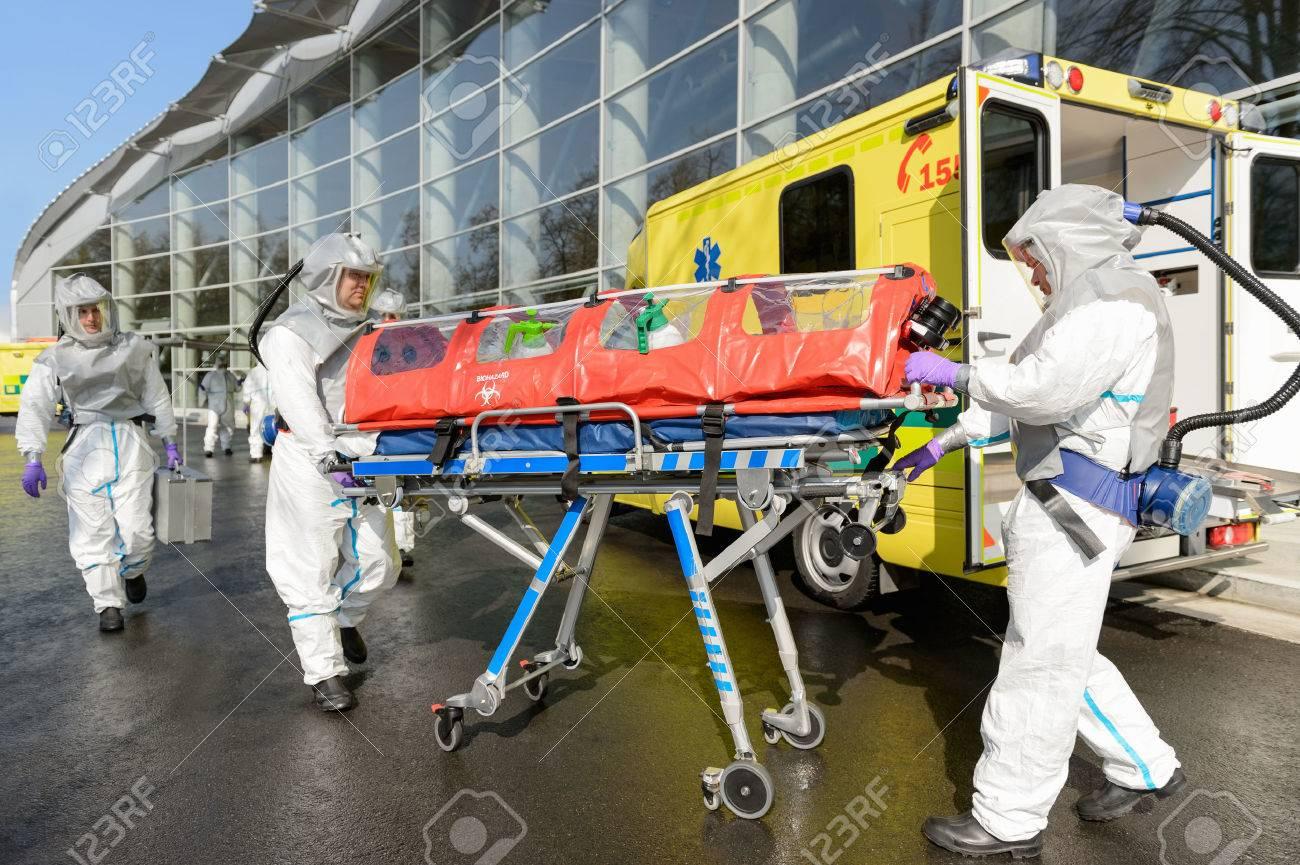 équipe médicale de matières dangereuses poussant civière en ambulance dans la rue Banque d'images - 28450714