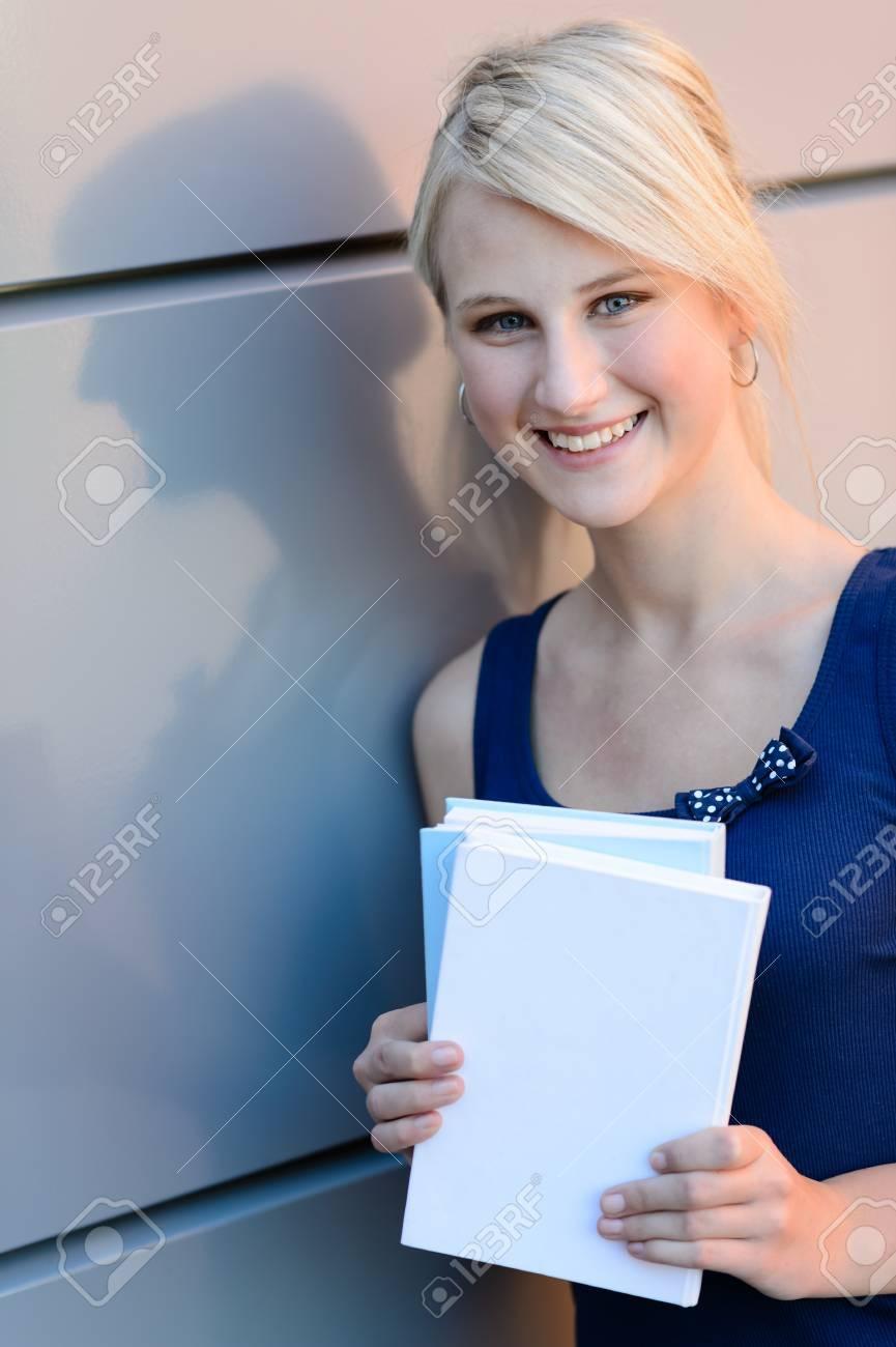 f38218140 Sonriente niña rubia estudiante con libros fuera apoyado contra la pared