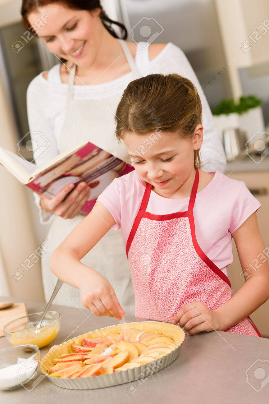 Young girl prepare home tart with mother adding sugar Stock Photo - 30413621