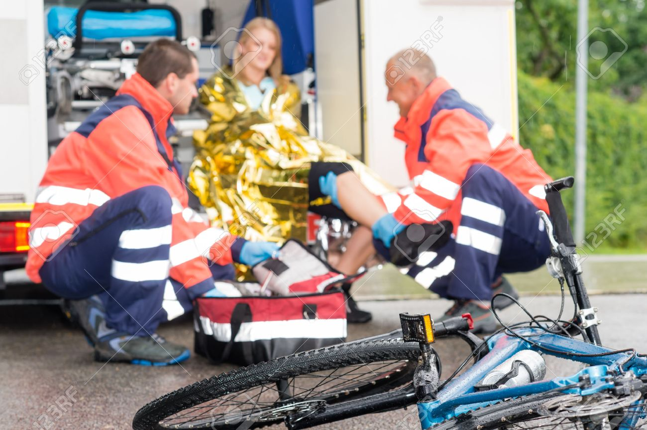 Accident bike woman get emergency help paramedics in ambulance Standard-Bild - 30414234