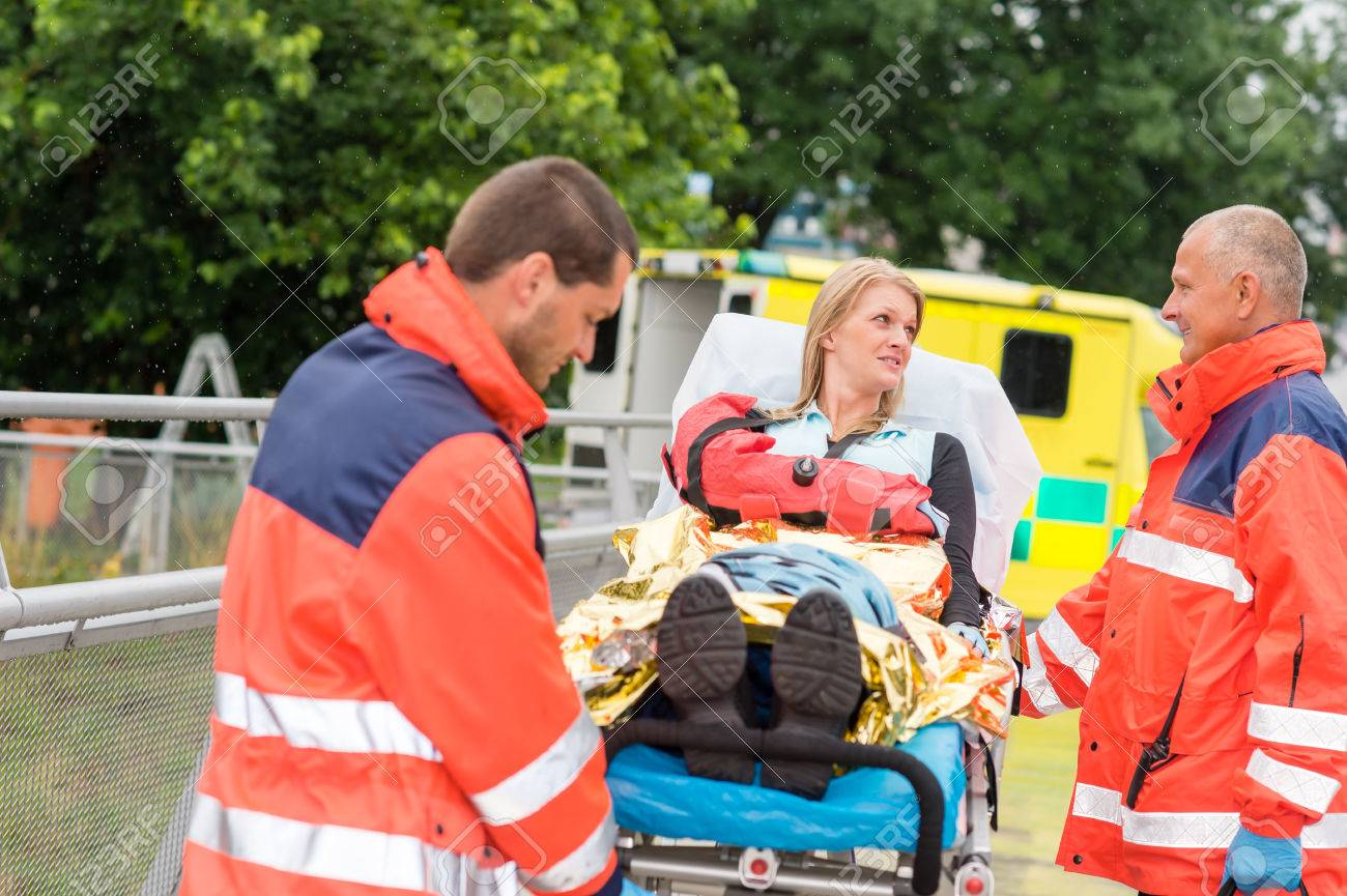 Patient talking with paramedics after accident  aid emergency arm injury Standard-Bild - 30414235