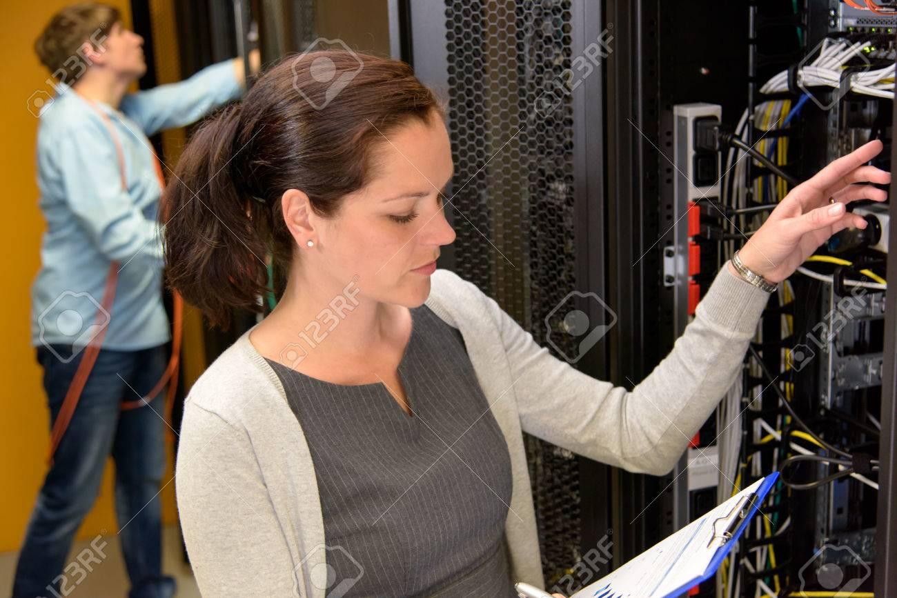 Femme gestionnaire de centre de données dans la salle de serveur connexions réseau de contrôle Banque d'images - 43324760
