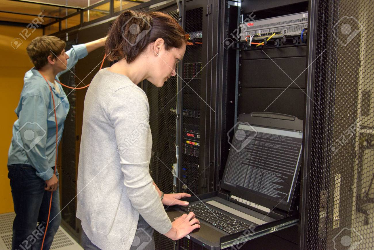 Female technician in server room checking network security with laptop Standard-Bild - 43324786