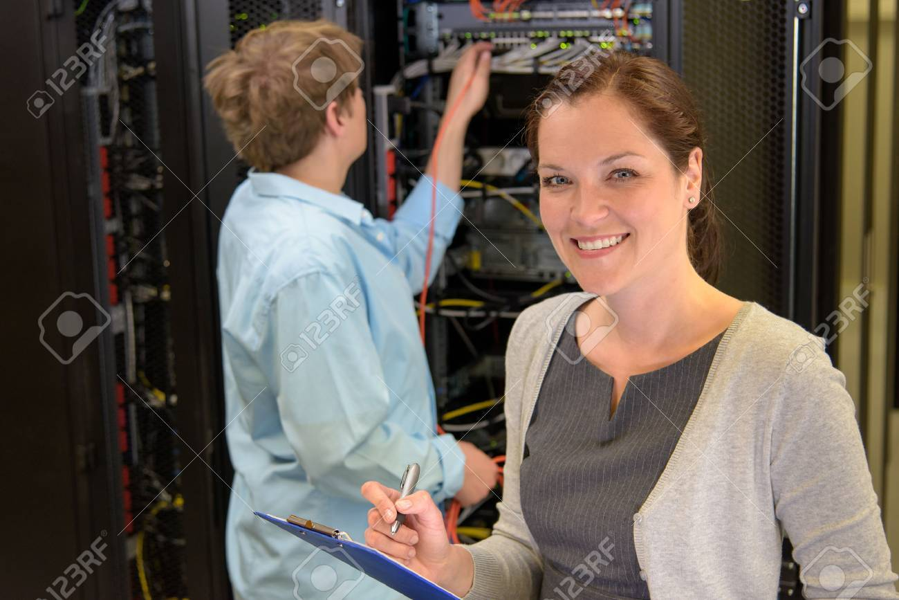 Two network engineers in server room checking computers Stock Photo - 43324790