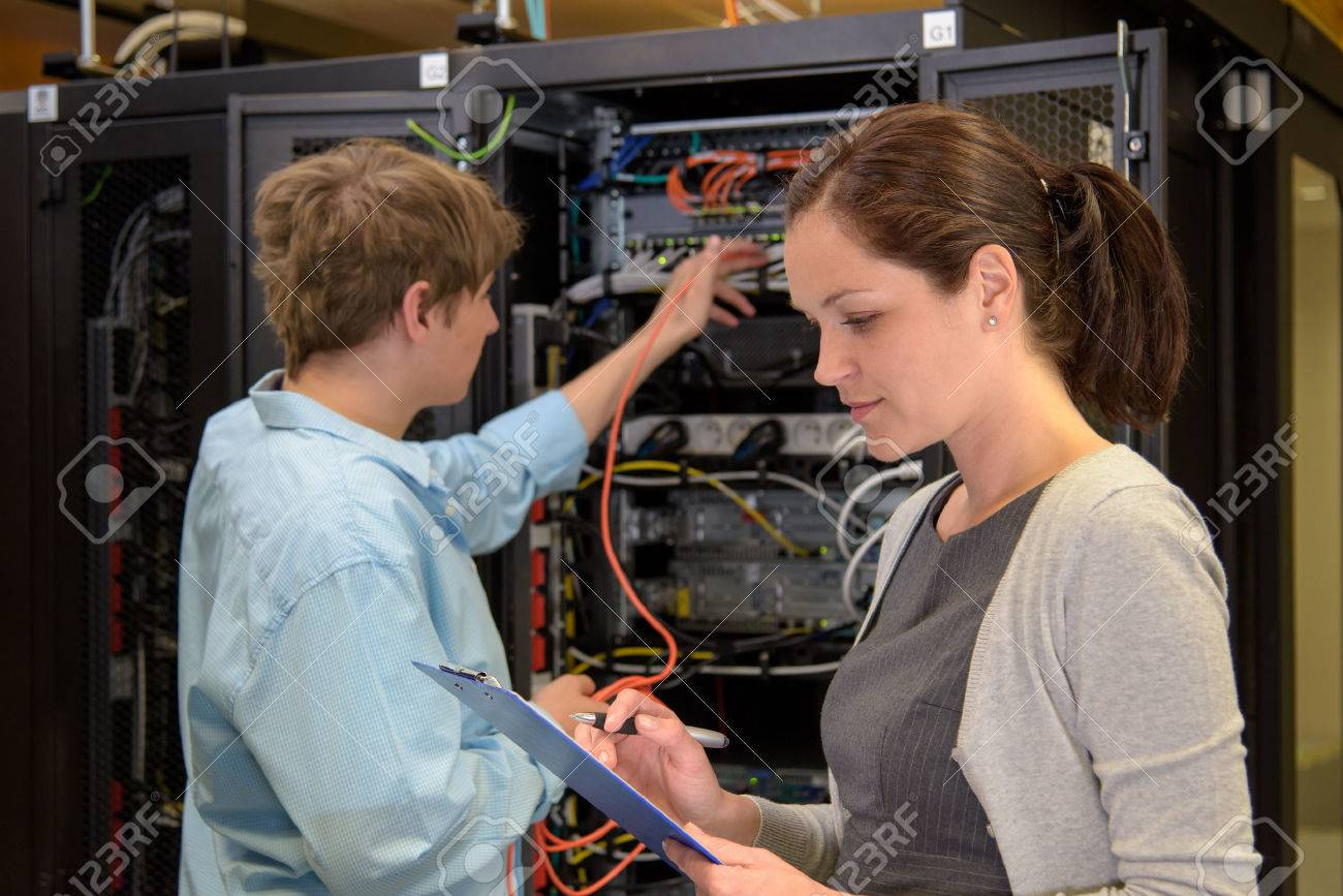 Team of IT specialists in datacenter working by network servers Stock Photo - 43324792