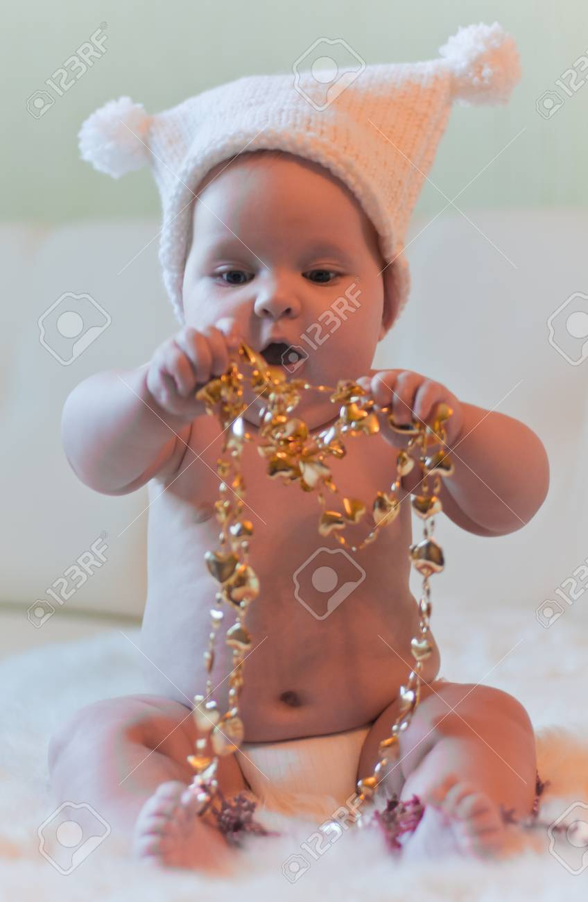 Baby in hat plays with gold tinsels Stock Photo - 12544598